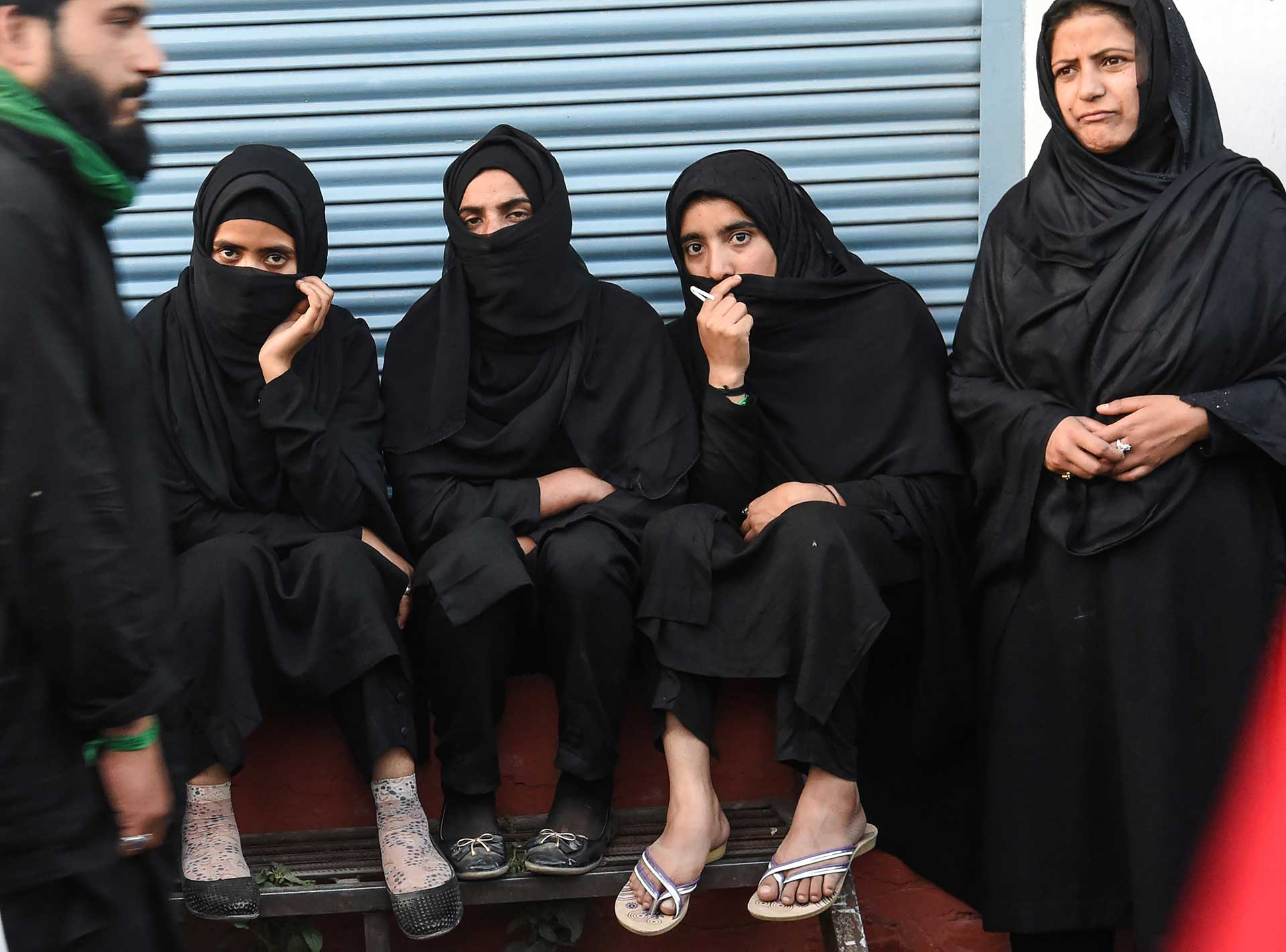 Un grupo de mujeres observa cómo los hombres se azotan a sí en Pakistán (AFP)