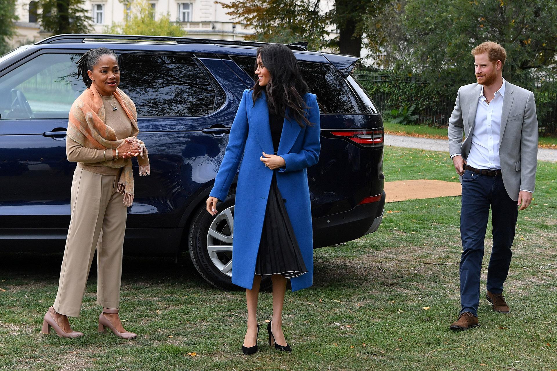 Meghan eligió un look formal, compuesto por un outfit negro y un elegante tapado azul