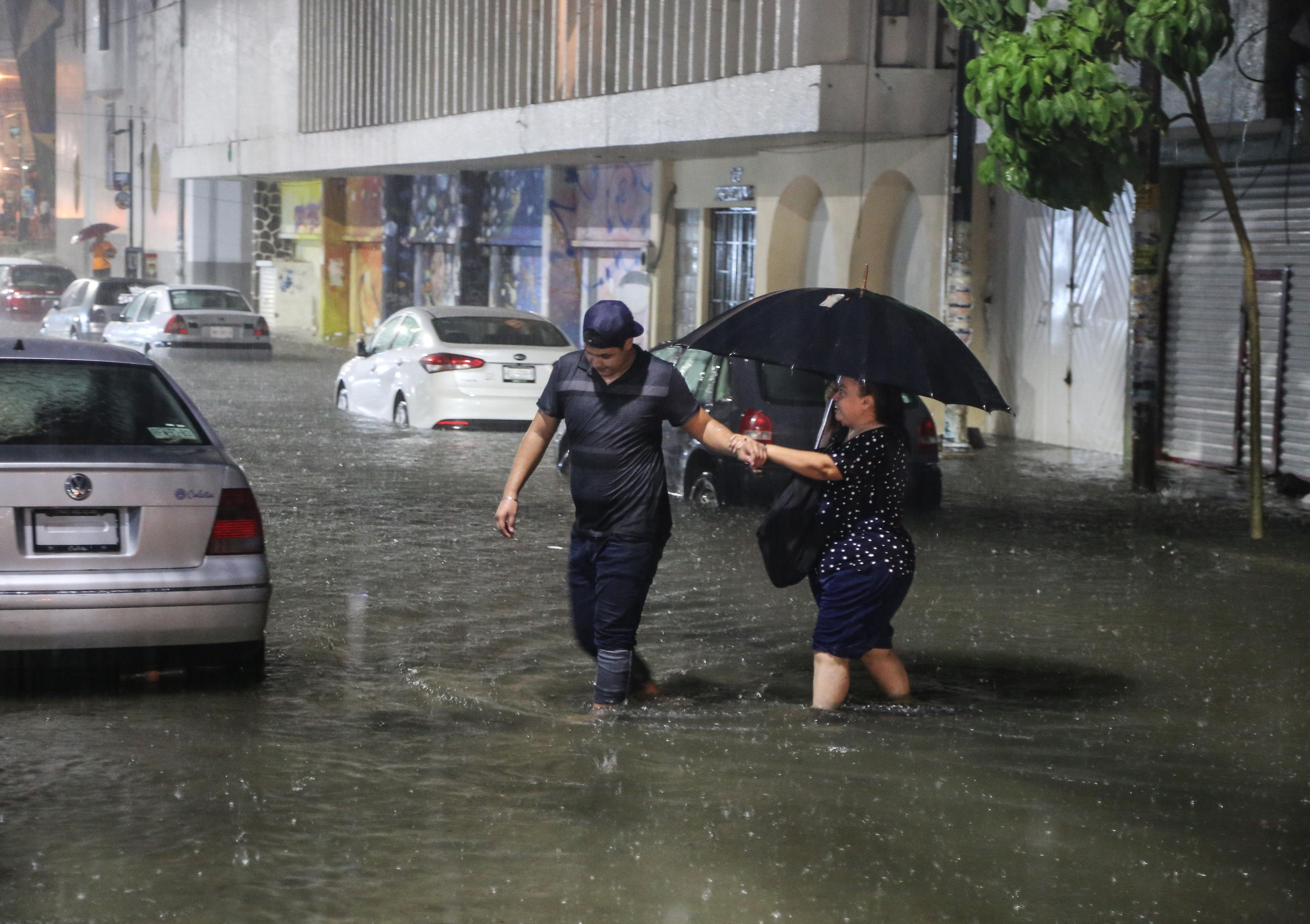 Dos personas cruzan una calle inundada n el puerto de Acapulco. (EFE/David Guzmán)