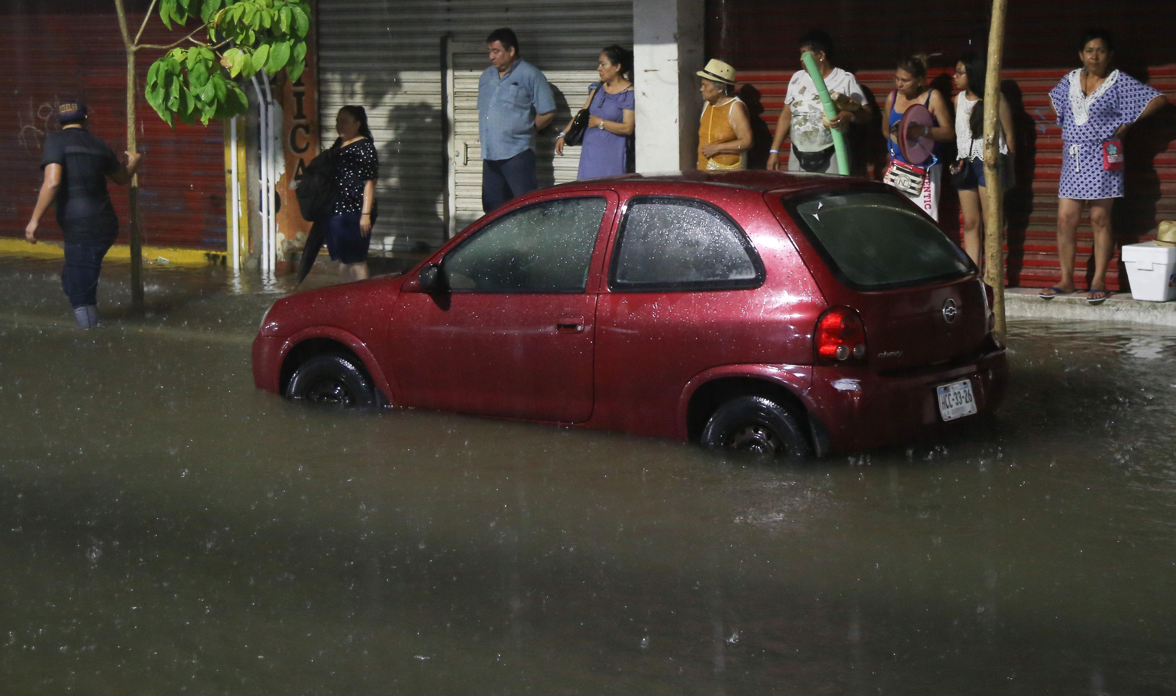 Un grupo de personas se cobijan de la lluvia, en una calle inundada, en el puerto de Acapulco, en el estado de Guerrero. (EFE/David Guzmán)