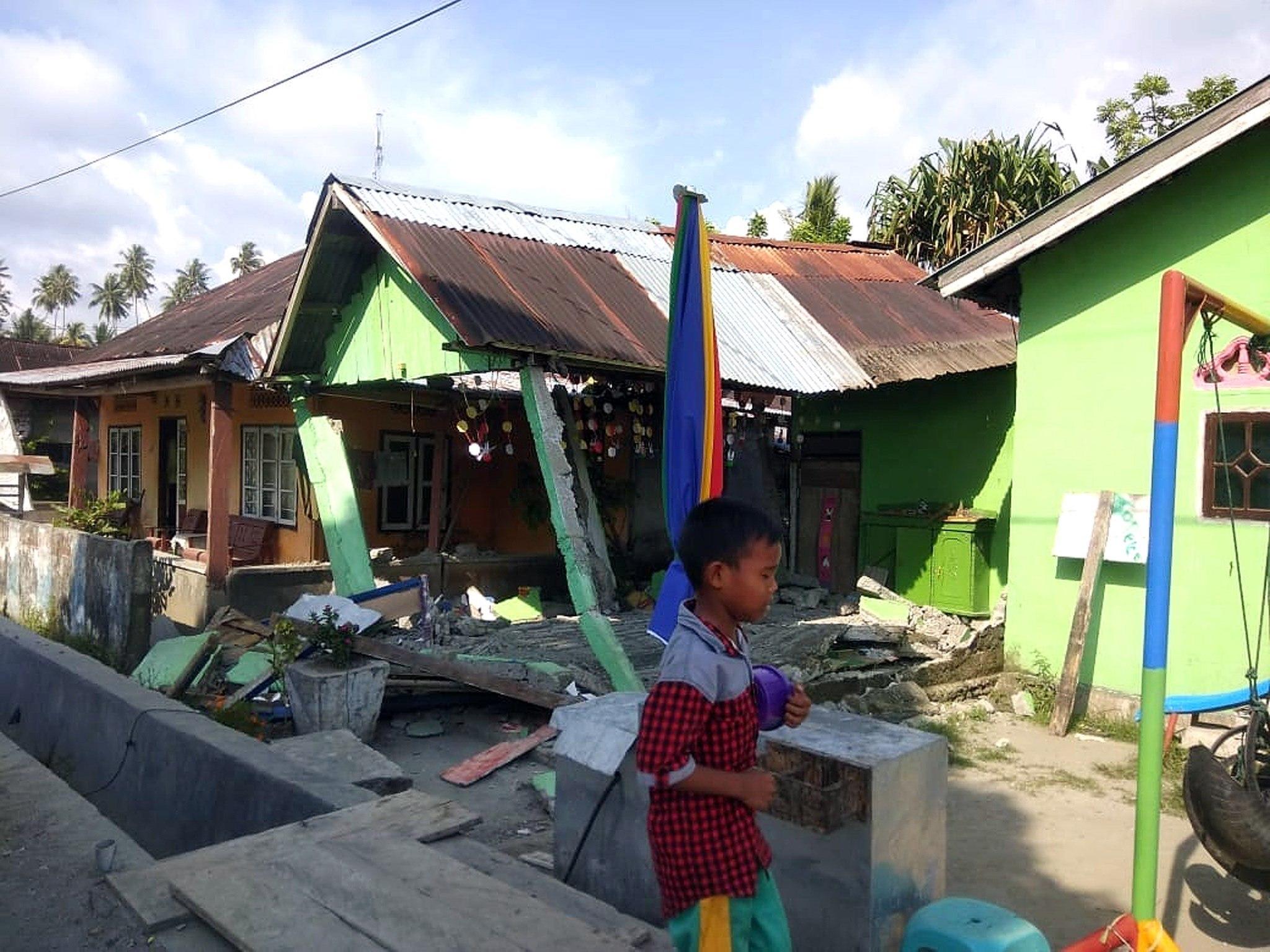 Un niño camina entre los escombros de una casa tras un terremoto de magnitud 7,5 que sacudió la isla de Célebes, situada en el norte de Indonesia. (EFE)