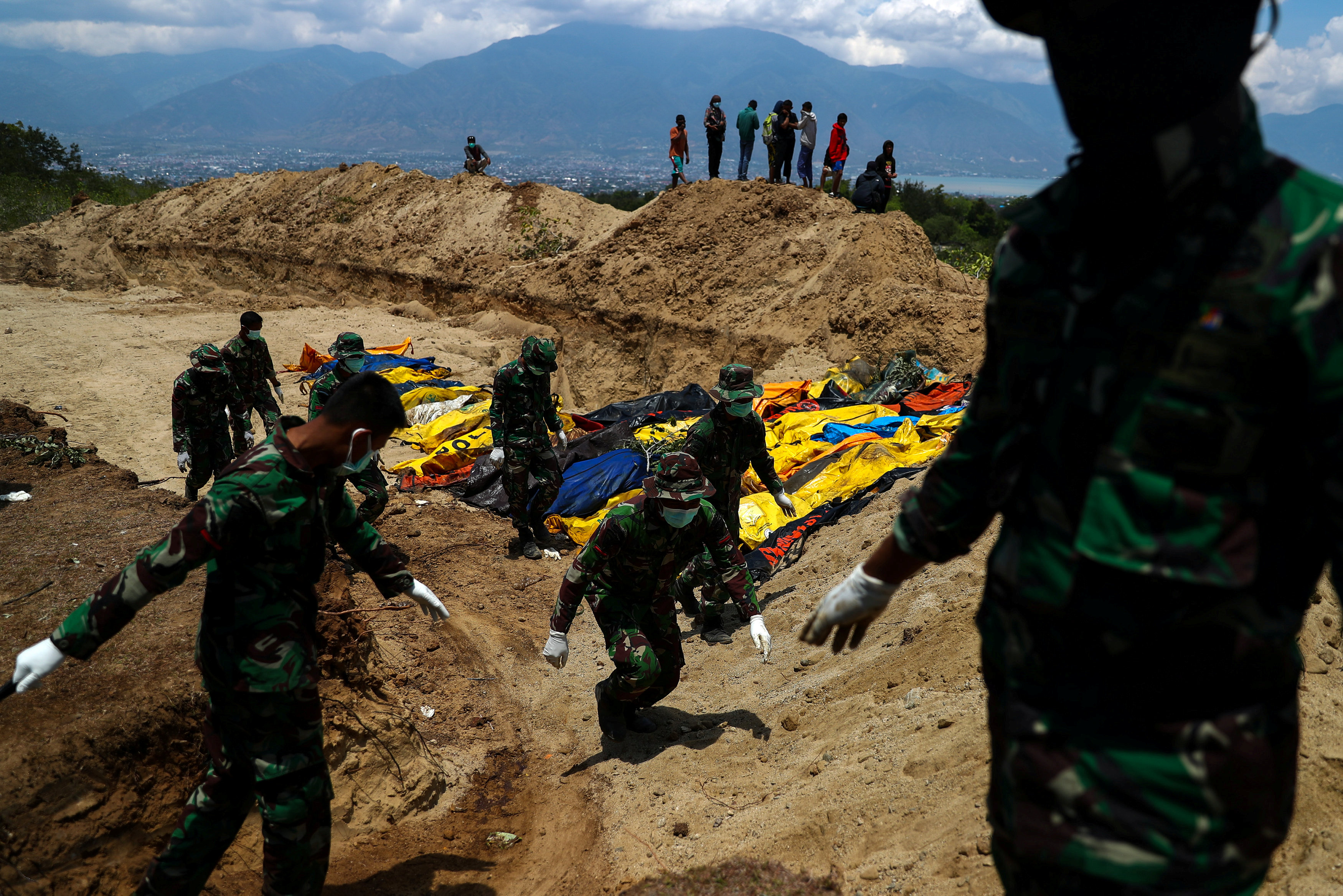 Soldados sepultan los cuerpos de víctimas del terremoto en una fosa común en el cementerio de Poboya en Palu (REUTERS/Athit Perawongmetha)