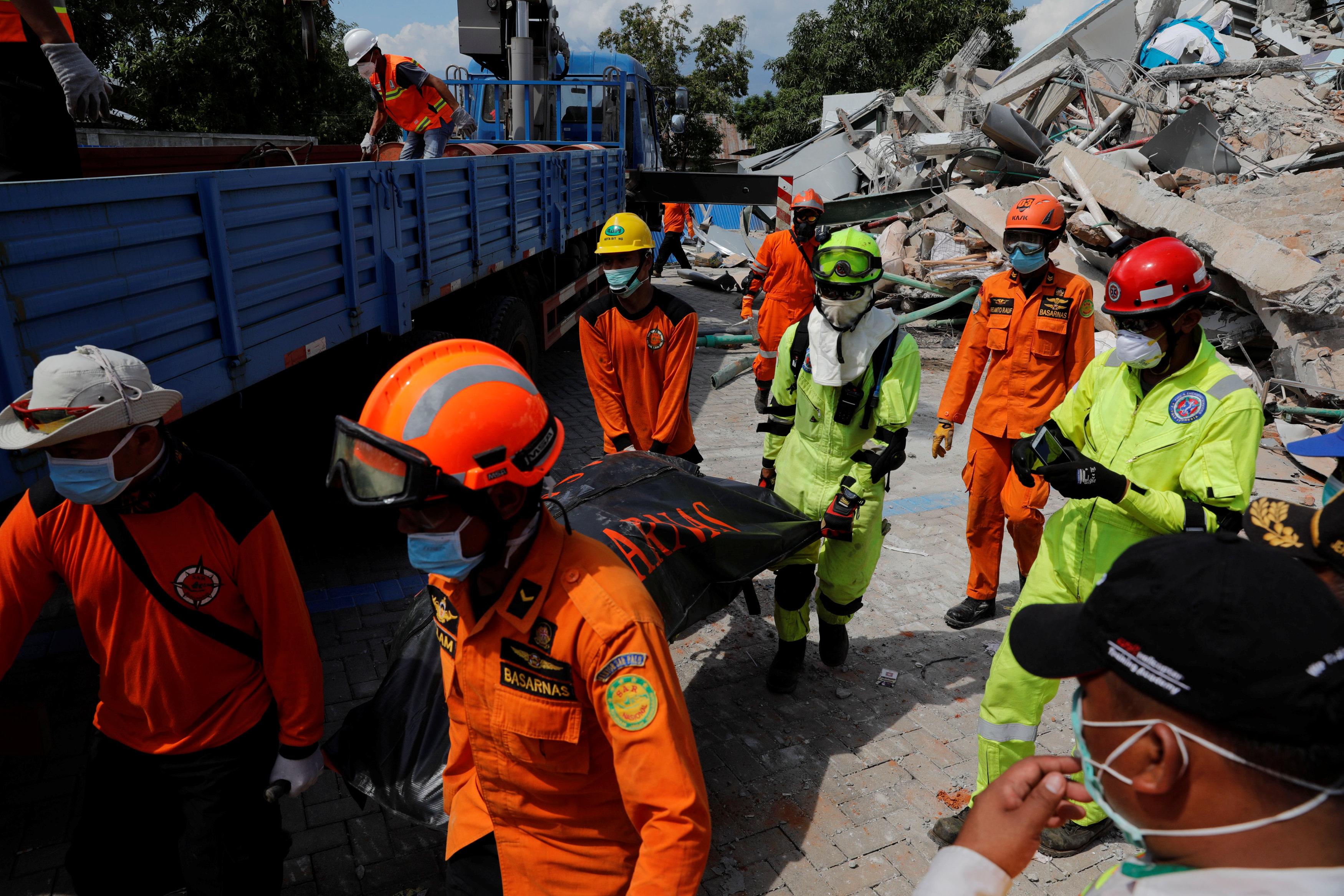 Socorristas cargan el cuerpo de una persona fallecida en el derrumbe del hotel Roa-Roa en Palu (REUTERS/Beawiharta)