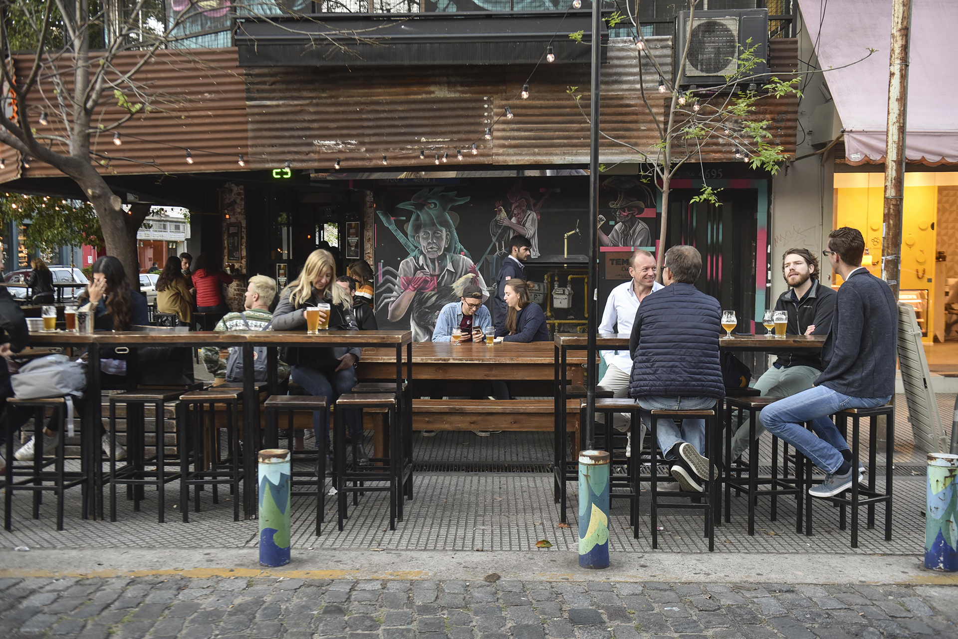 Esquina de Costa Rica y Gurruchaga, donde las cervezas unen a las generaciones. Una excelente ubicación para ir por unas cervezas y compartir con amigos. Mesas compartidas y banquetas altas en las afueras de la cervecería. El graffiti de la cervecería está realizado por Cris Herrera Kiki