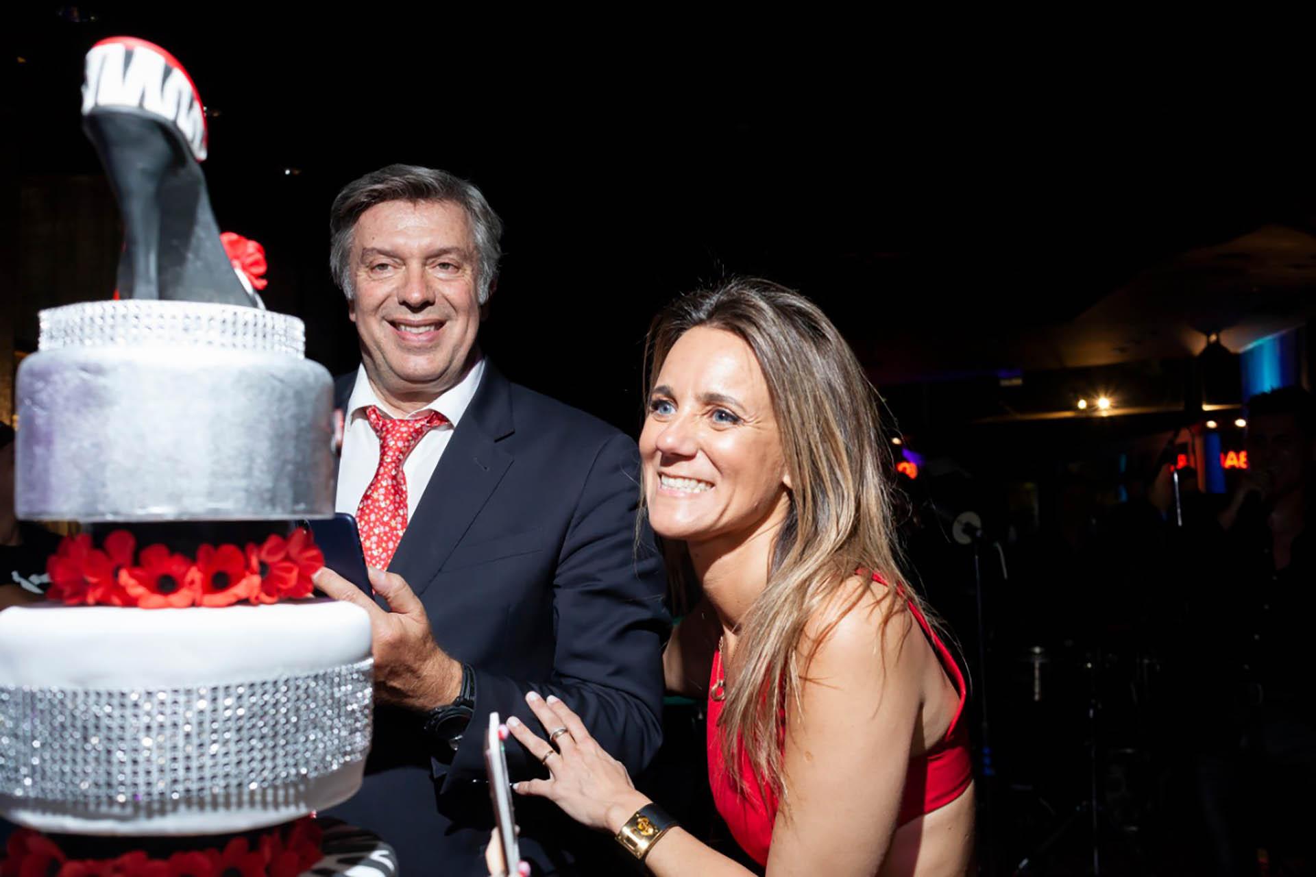 La pareja frente a la torta de tres pisos con los que la doctora festejó los 40