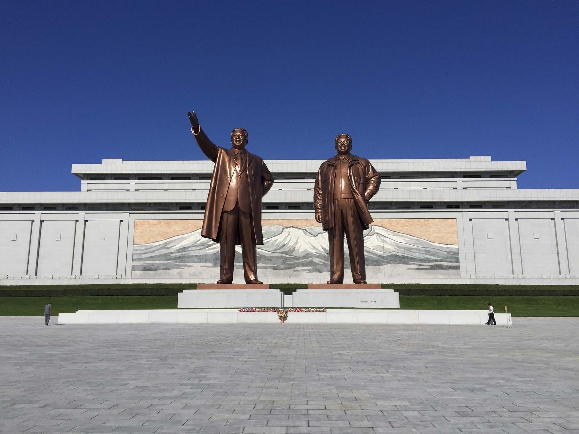 Las estatuas de bronce de veinte metros, fabricadas por el estudio oficial de arte Mansudae y emplazadas en una de las colinas principales de Pyongyang, muestran la mejor cara de los líderes muertos. No dan indicios del tumor en la nuca de Kim Il Sung, que creció hasta alcanzar el tamaño de una pelota de tenis y le provocó la muerte en 1994, a los ochenta y dos años, y exhiben a un Kim Jong Il con una altura y una bonhomía que no conoció en vida