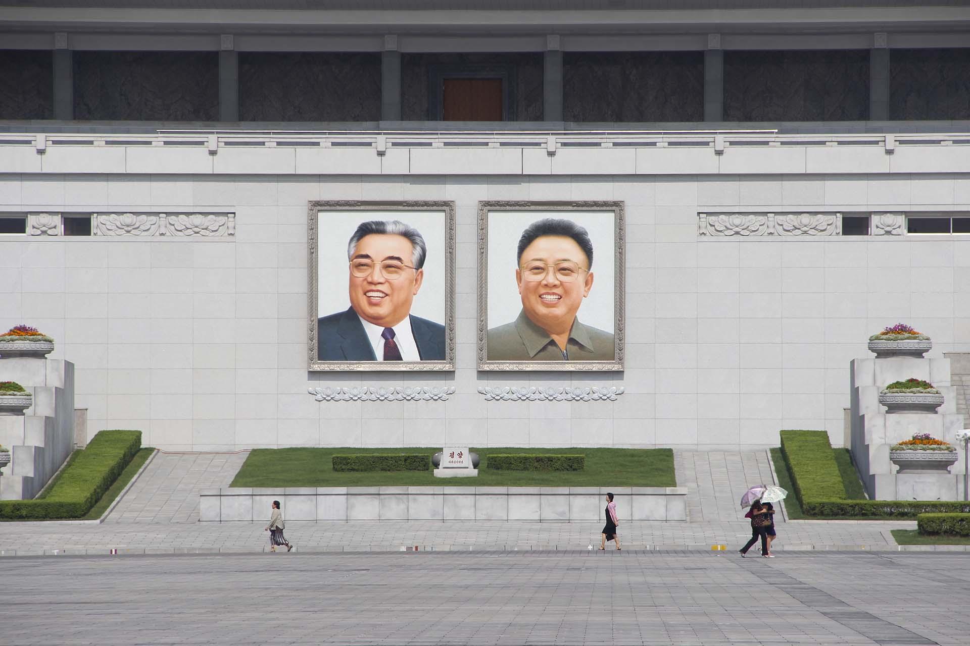 """Los retratos de Kim Il Sung (izq.) y Kim Jong Il (der.) dominan la plaza central de Pyongyang. Cuando llegué por primera vez a la ciudad, era el año 104. La noche anterior, al salir de Pekín, el almanaque chino decía """"2015"""", pero esa convención no tenía valor al otro lado de la frontera. Allí marcaba el paso de los días el calendario Juche, una creación plenamente norcoreana que fija el inicio de los tiempos en 1912, el año en que nació Kim Il Sung, """"Presidente Eterno"""" de Corea del Norte aun después de su muerte"""