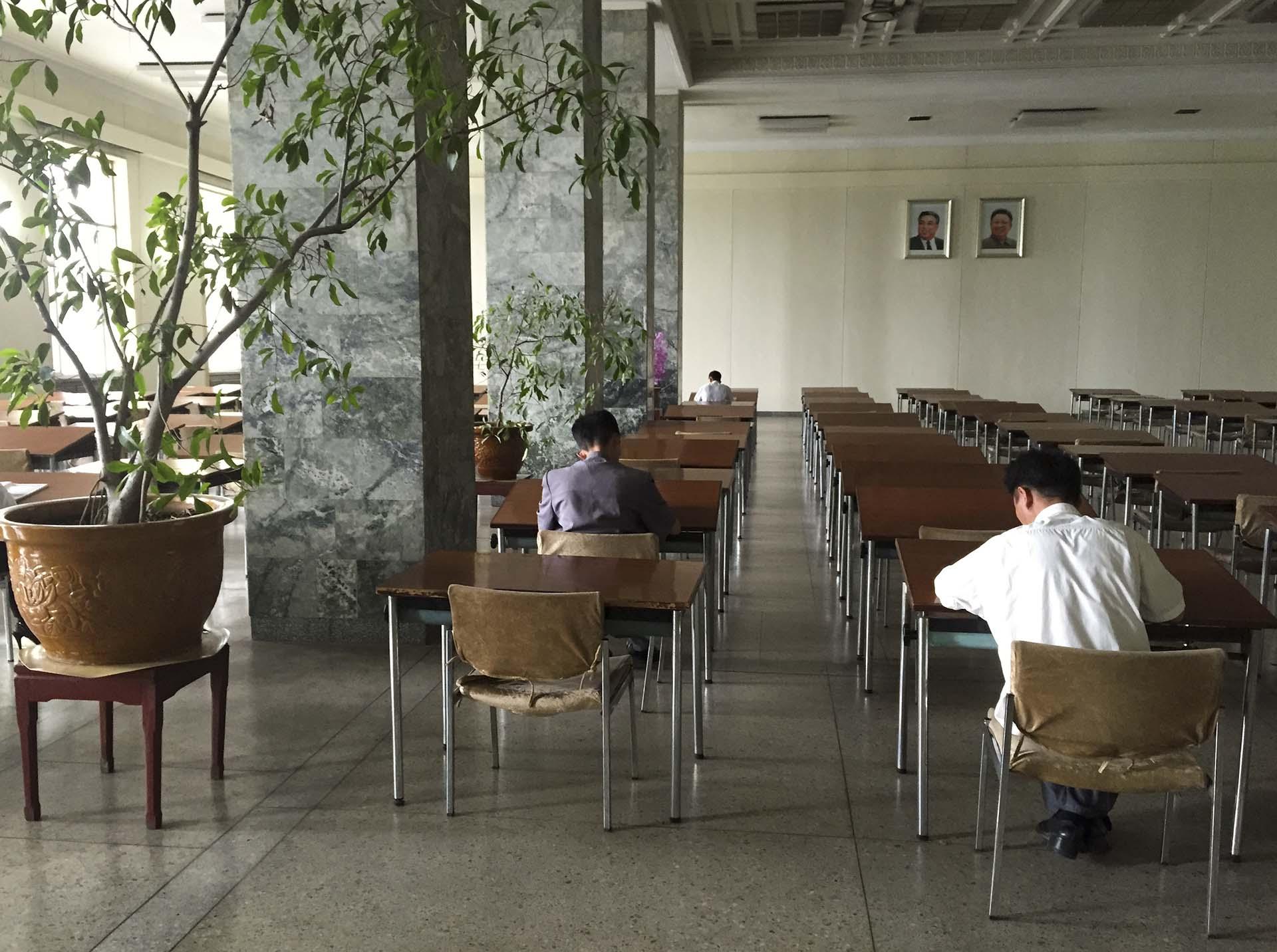 En la Gran Casa de Estudios del Pueblo, que oficia de biblioteca central de Pyongyang y es uno de los pocos edificios públicos en los que un extranjero puede ver las computadoras con acceso a la intranet norcoreana aunque no pueda usarlas, tomamos el ascensor de madera hasta el segundo piso, donde estaba la sala de lectura, una habitación presidida, como todas en aquel lugar, por los retratos de los dos Kim