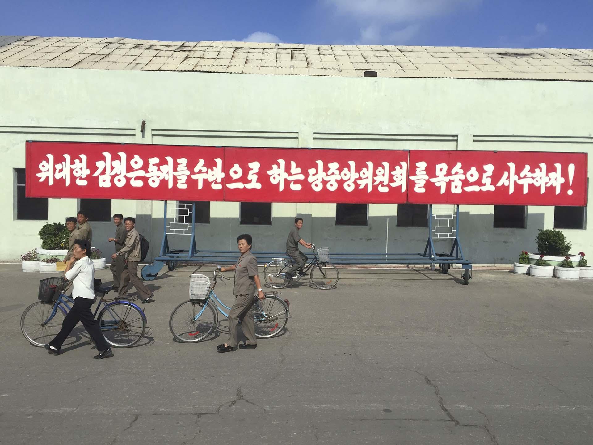 """Cuando llegamos con nuestro micro turístico a media mañana, un grupo de trabajadores ingresaba para cumplir su turno en la planta de fertilizantes de la ciudad de Hamhung, cerca del Mar del Este. No parecían cautivados, como nosotros, por el enfático cartel rojo a sus espaldas, donde se leía: """"¡Debemos defender el Comité del Partido que acompaña a nuestro Gran Camarada, Kim Jong Un!"""""""