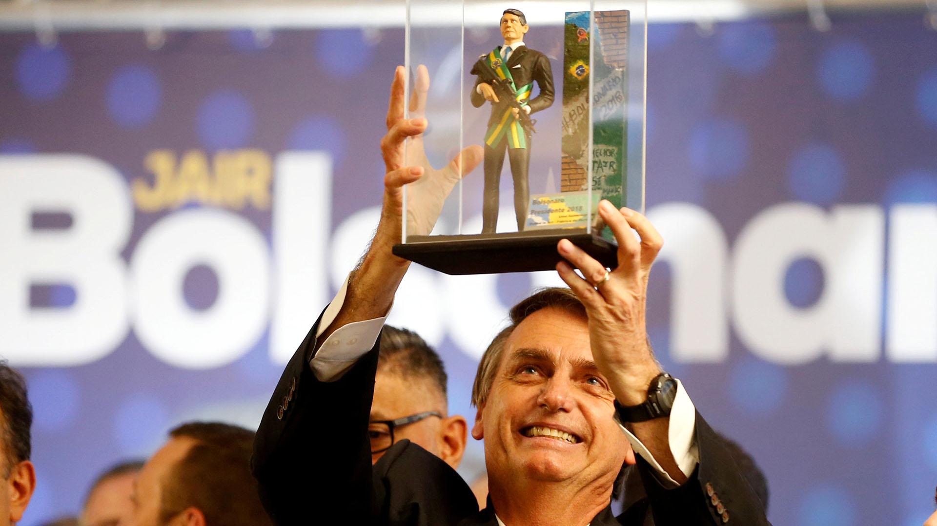 Jair Bolsonaro levanta un muñeco de él con la banda presidencial, sosteniendo un fusil de asalto, durante un acto en Curitiba en marzo pasado (REUTERS/Rodolfo Buhrer/File photo)