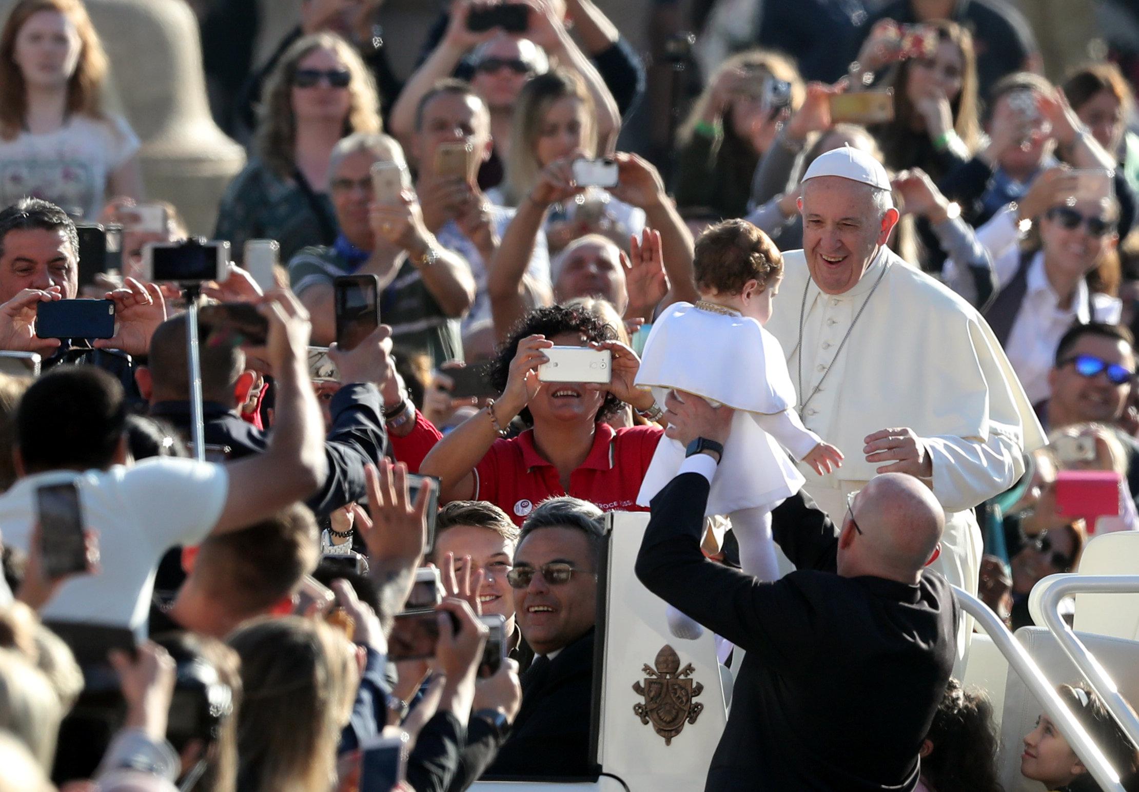 El papa con un bebé durante la audiencia del miércoles (REUTERS/Tony Gentile)
