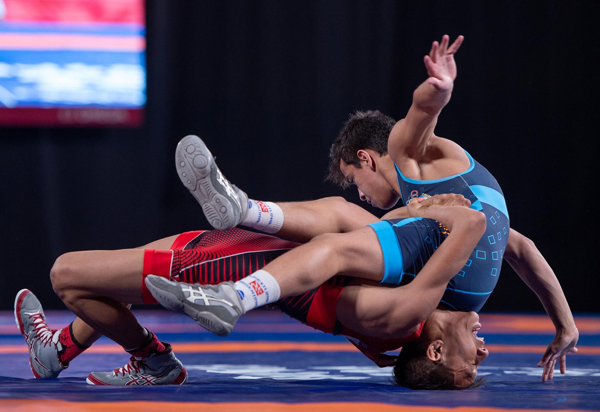 El mexicano Axel Andre Salas Esquivel, de rojo,lucha ante el argentinoEduardo Lovera, de azul en la categoría hasta 51kilos(Foto:REUTERS)
