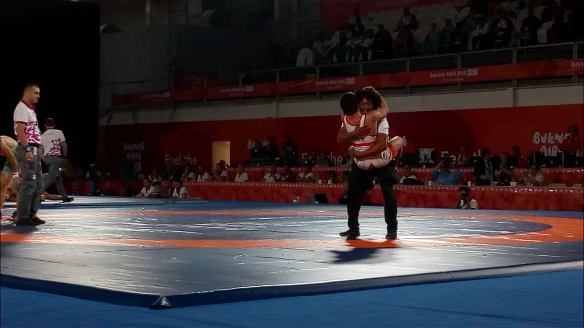 David Almendra celebra su triunfo en semifinales de lucha libre con su profesor cubano