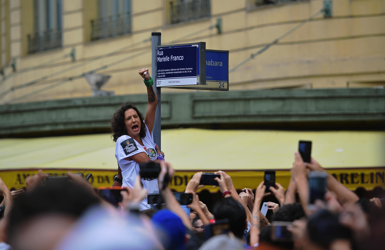Teresa Benicio, viuda de Mariella Franco, reemplaza la placa con el nombre de la concejal asesinada (CARL DE SOUZA / AFP)
