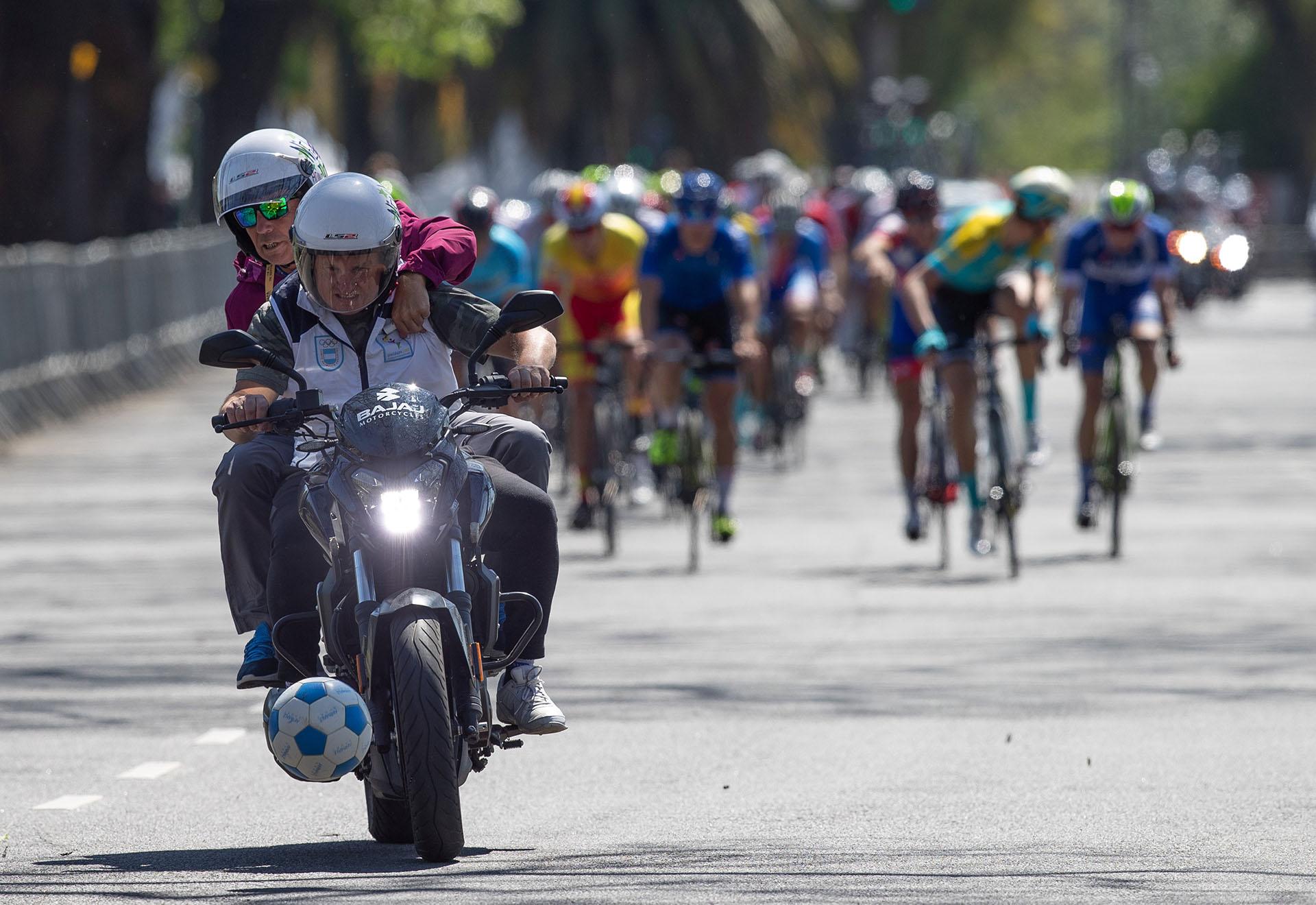 Un voluntario de la organización precede en moto la carrera de ciclismo masculino en busca de quitar de la pista un balón que apareció repentinamente ( REUTERS)