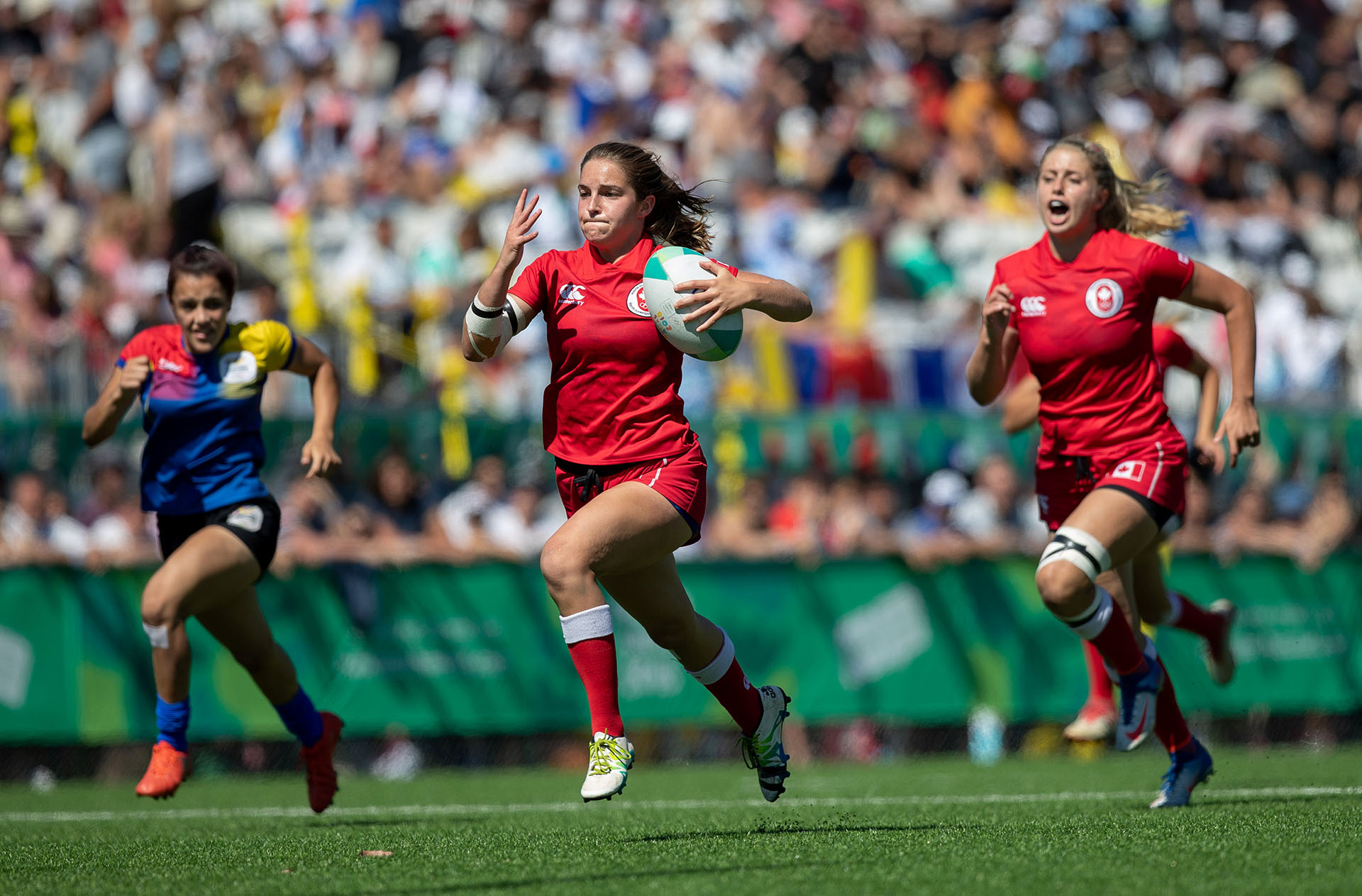 Taylor Black, de Canadá, corre con la pelota mientras la secunda su compañera Delaney Aikensdurante el partido por la medalla de Bronce del Rugby Seven de Mujeres disputado en el Club AtléticoSan Isidro de Buenos Aires(REUTERS)
