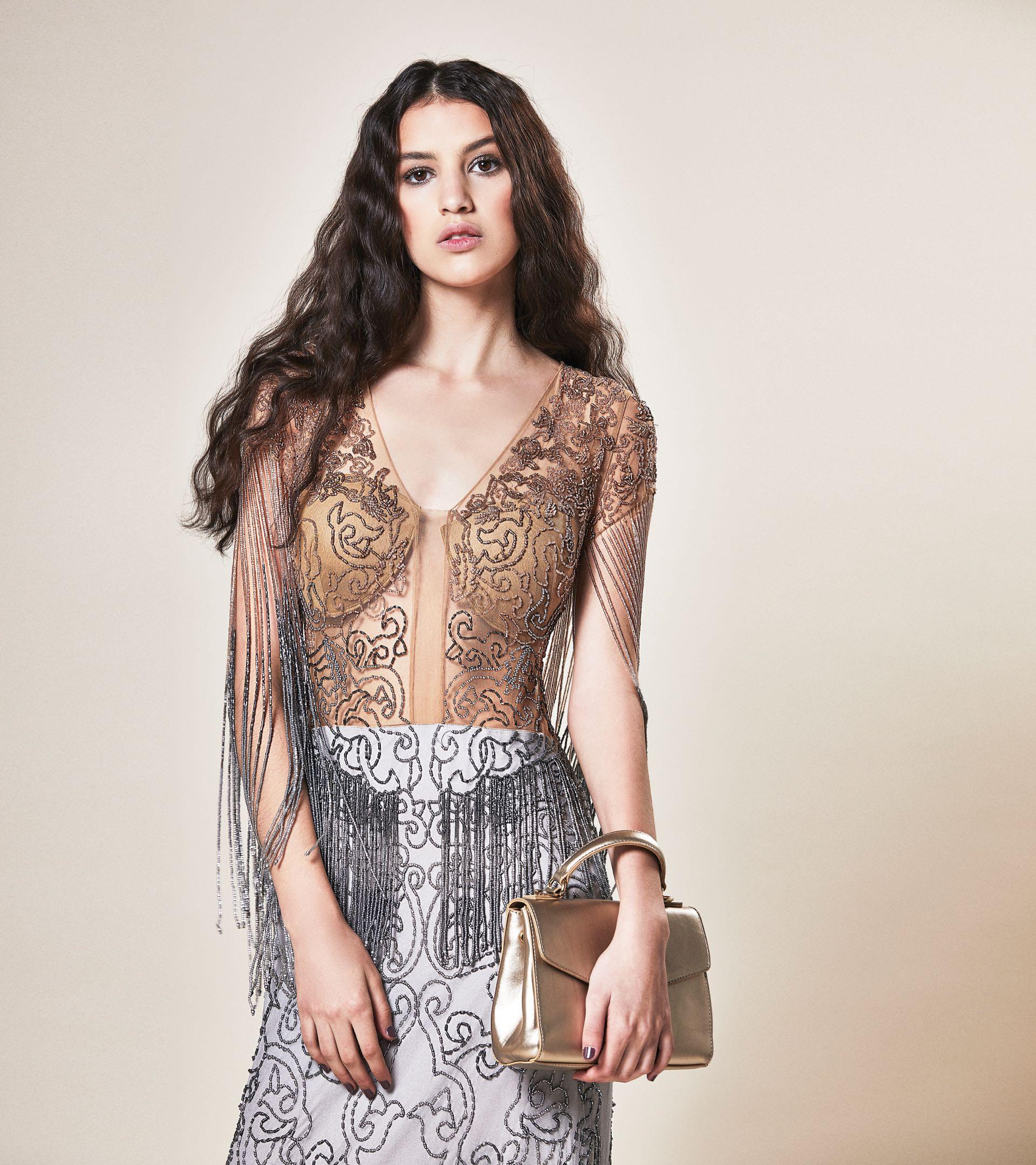 Vestido de encaje de algodón y flecos ($ 8.950, Carmela Achaval), zapatos de charol ($ 2.290, Viamo) y sobre con cadena ($ 2.300, Vitamina).