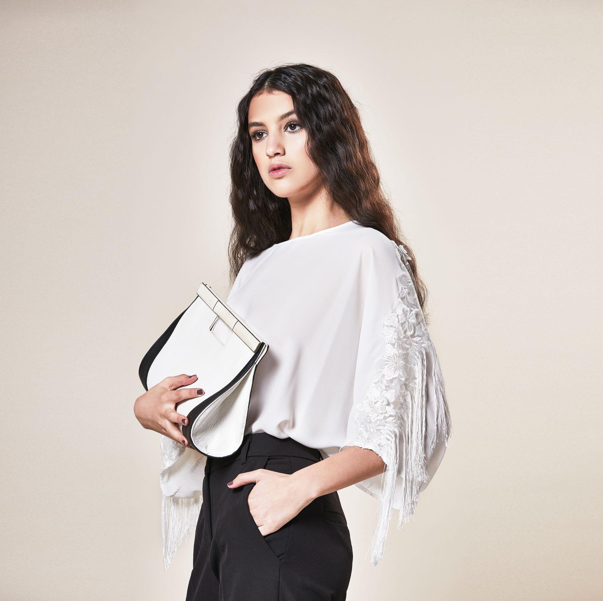 Blusa de gasa con encaje y flecos ($ 6.000, Rafael Garófalo), pantalón sastre($ 2.400, Ossira) y clutch de cuero y nácar (Casta by Analía).
