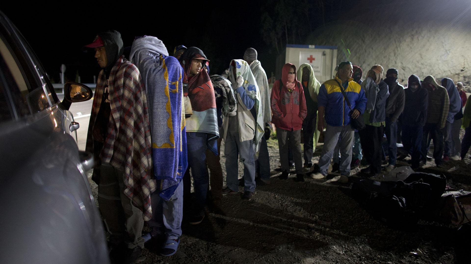 Migrantes hacen fila para recibir pan y café donado por una familia colombiana (AP Photo/Ariana Cubillos)