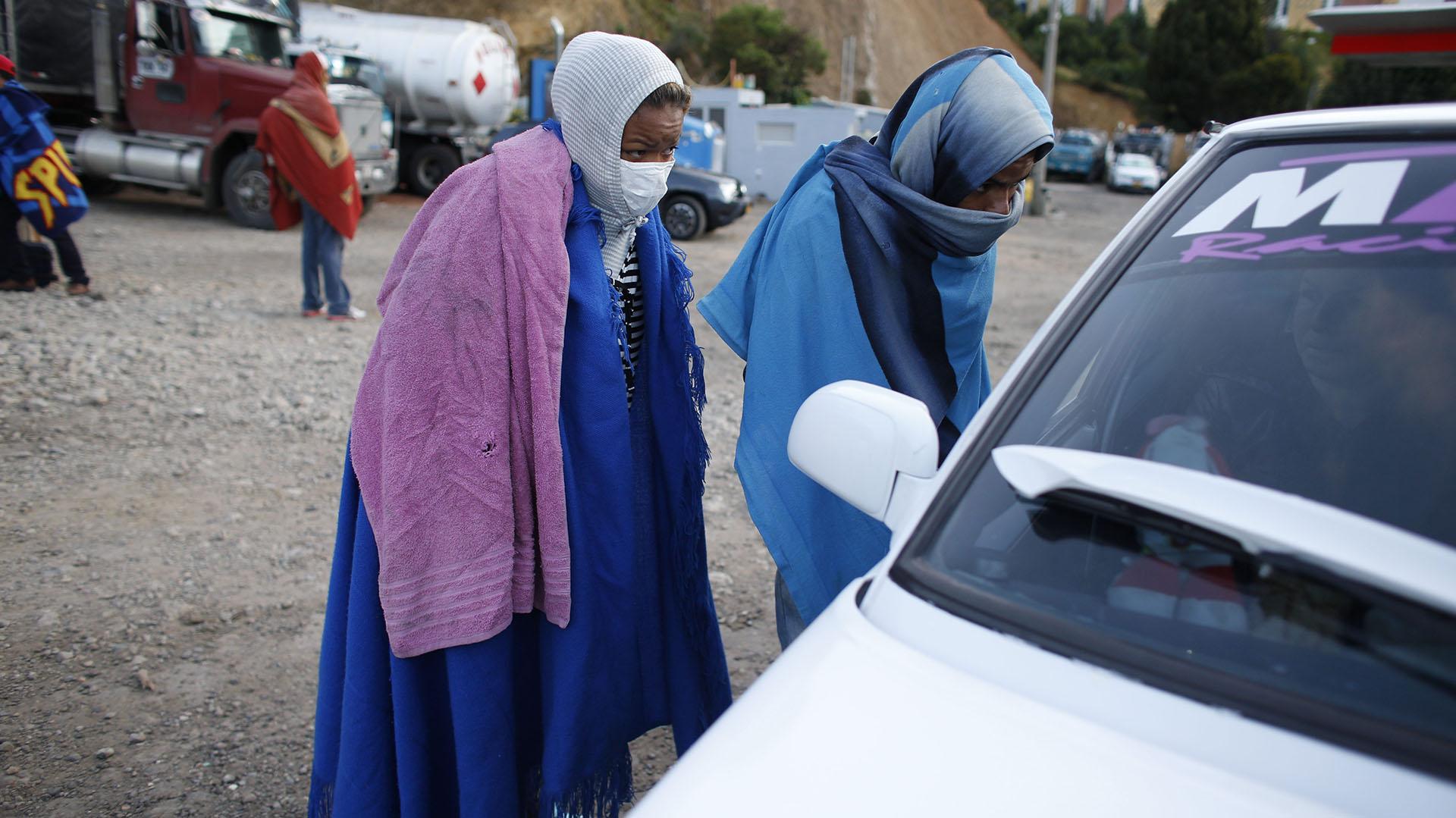 Los migrantes se envuelven en sábanas para combatir el frío en Bucaramanga (AP Photo/Ariana Cubillos)