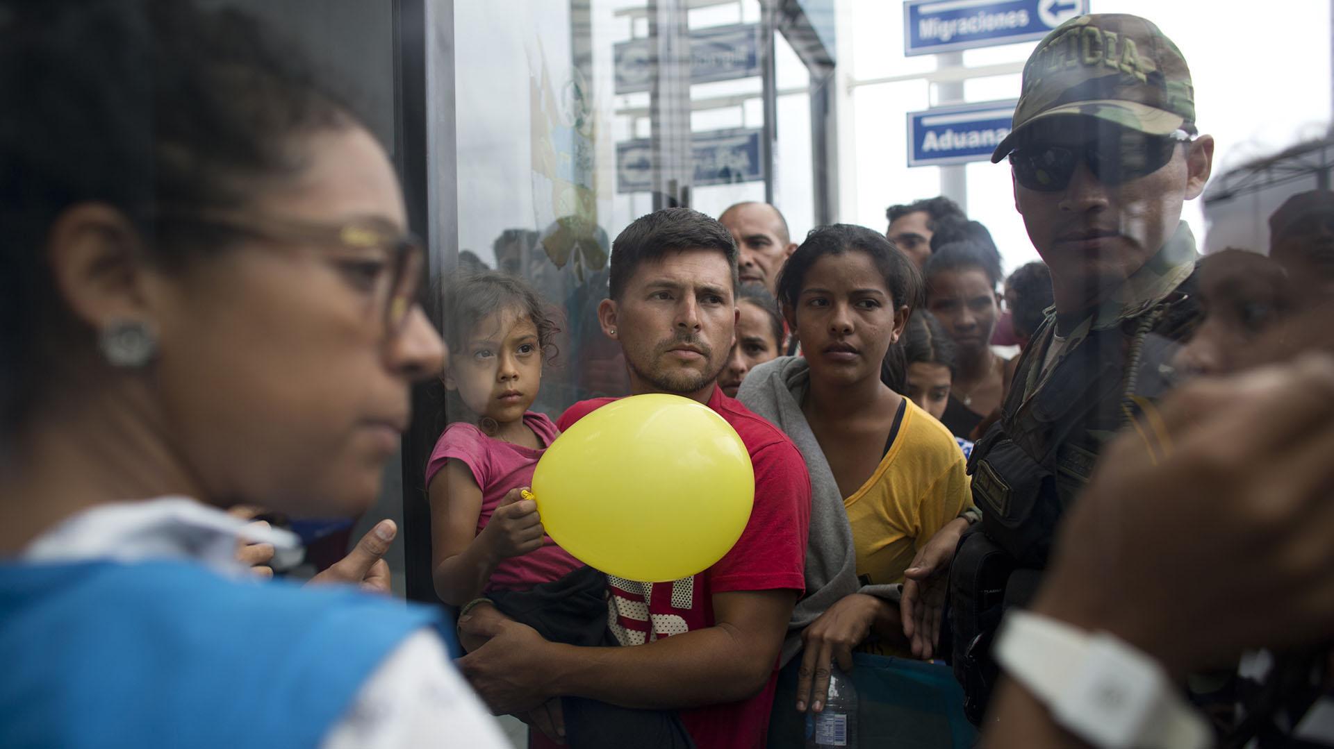Venezolanos esperan para ser atendidos por oficiales peruanos de migración en la frontera (AP Photo/Ariana Cubillos)