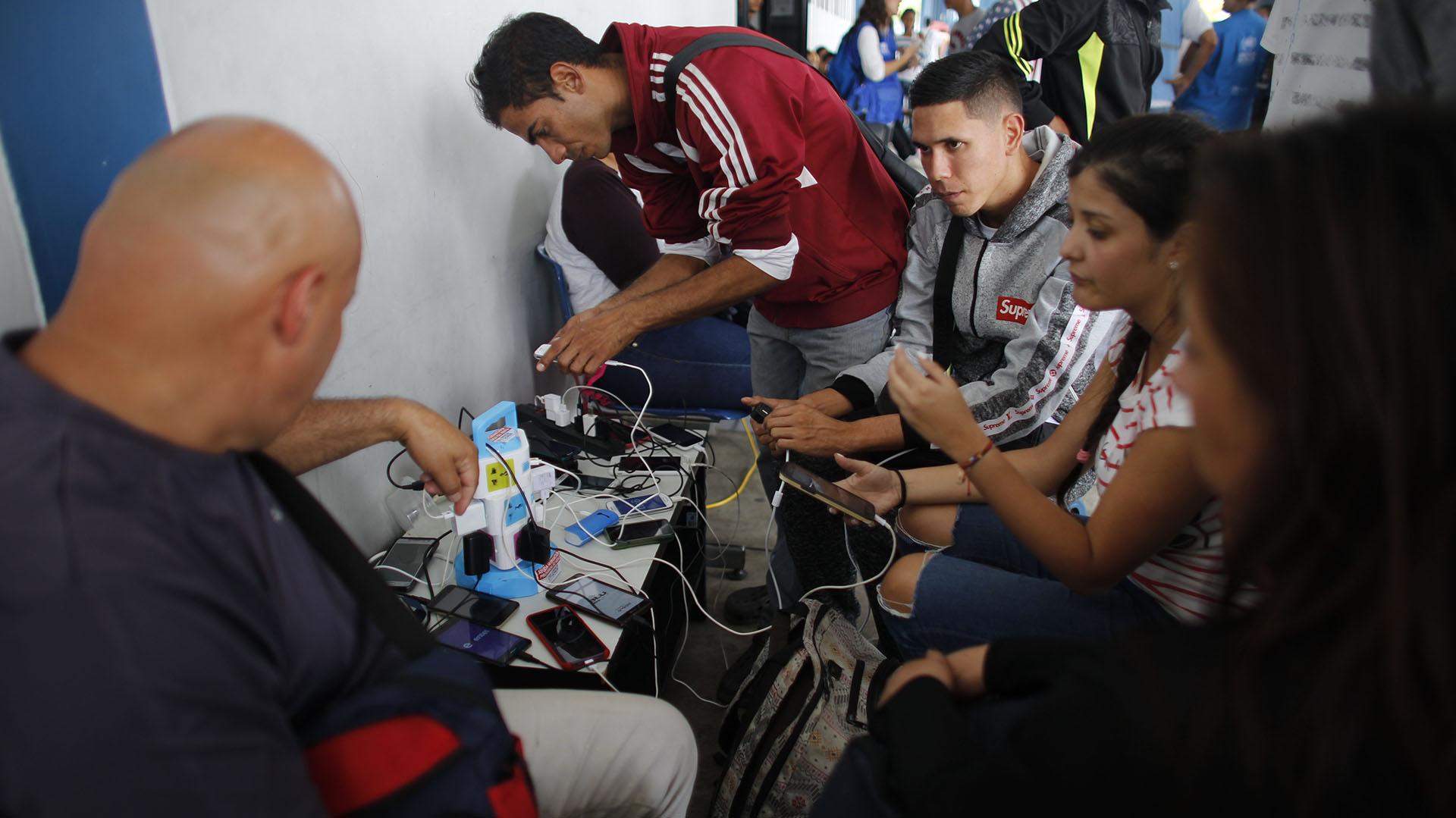 Mantener la carga de los teléfonos es una prioridad para los migrantes, que por momentos deben pasar largos períodos de tiempo sin posibilidad de contacar familaires (AP Photo/Ariana Cubillos)