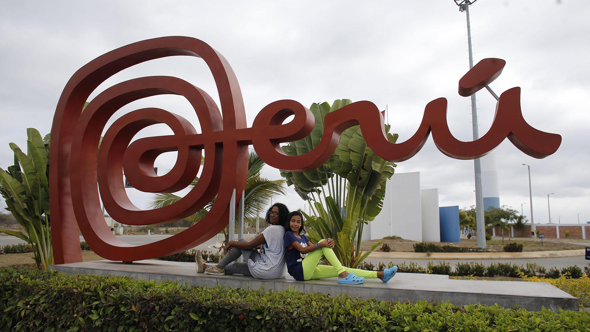 Sandra Cadiz y su hija posar tras llegar a su destino, Perú (AP Photo/Ariana Cubillos)