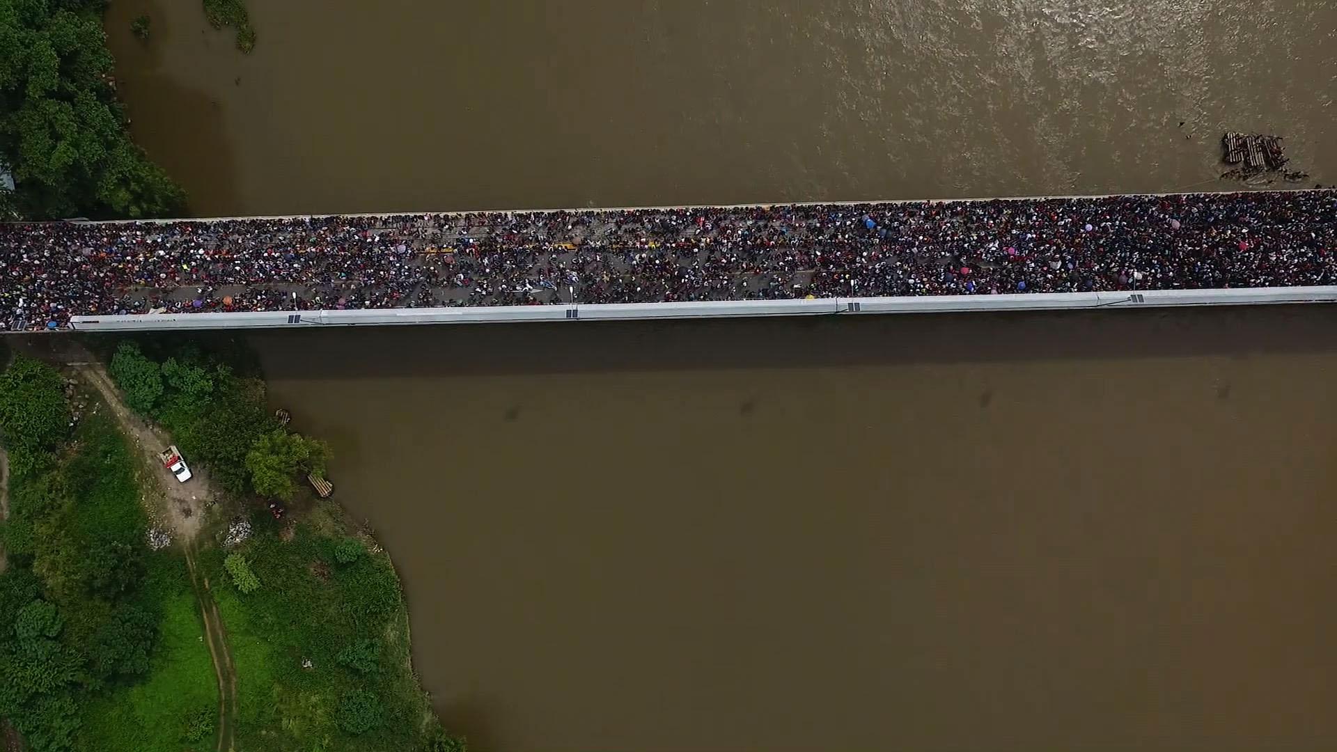 Imagen aérea de los migrantes esperando sobre un puente en la frontera en Honduras y México. (Photo by PEDRO PARDO / AFP)