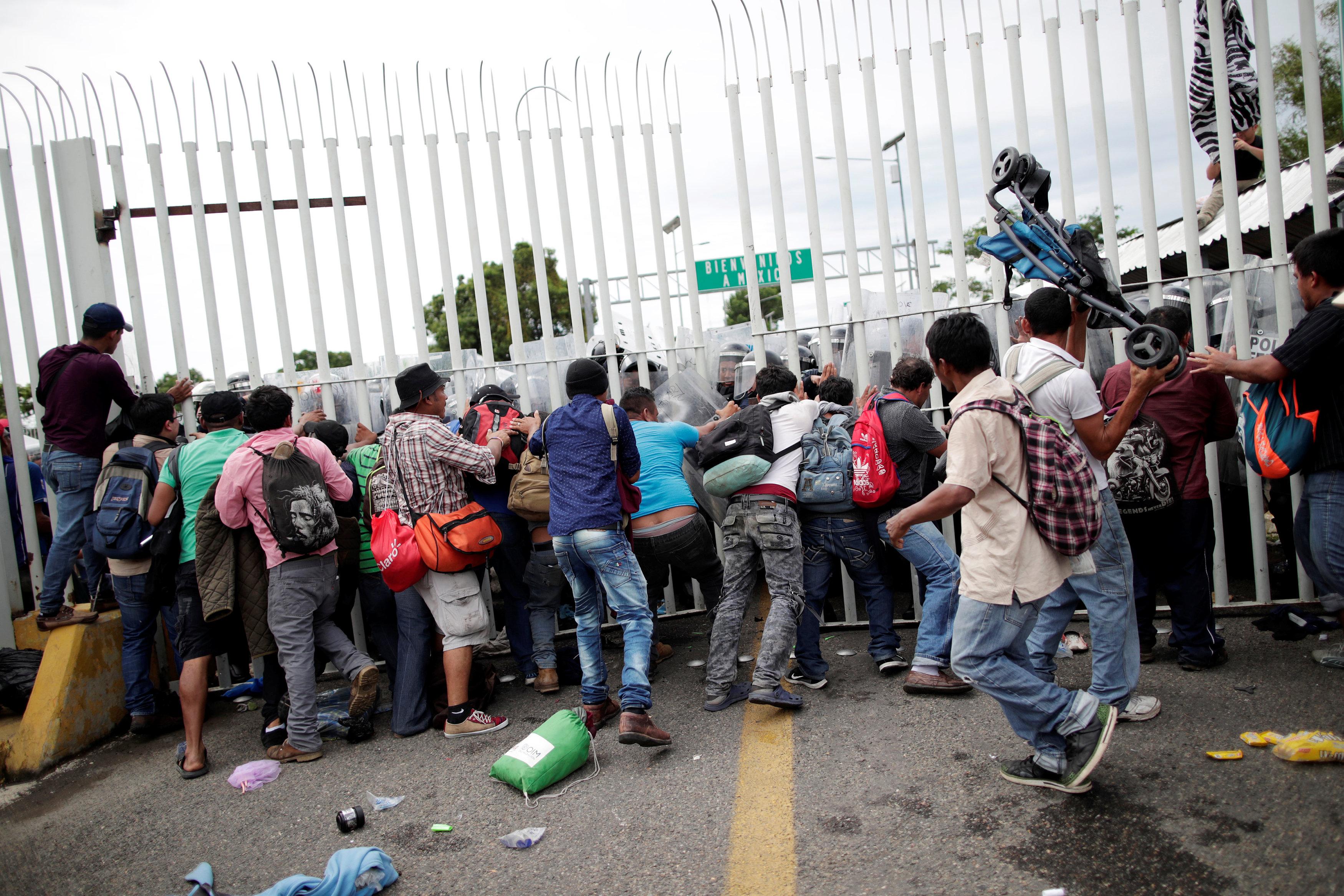 Migrantes empuja una reja en la frontera para pasar.