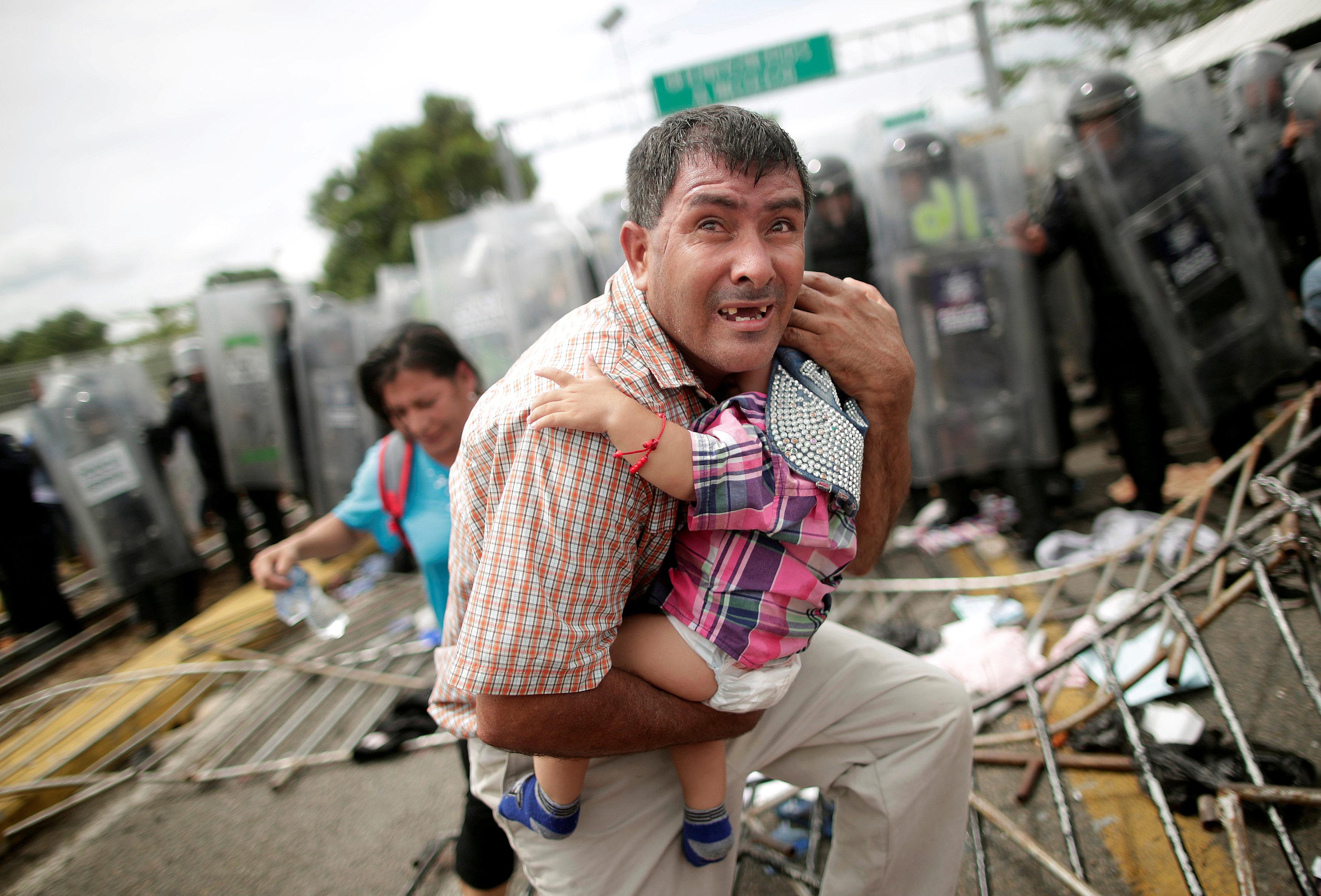 Un migrante hondureño protege a un bebé. (REUTERS/Ueslei Marcelino)