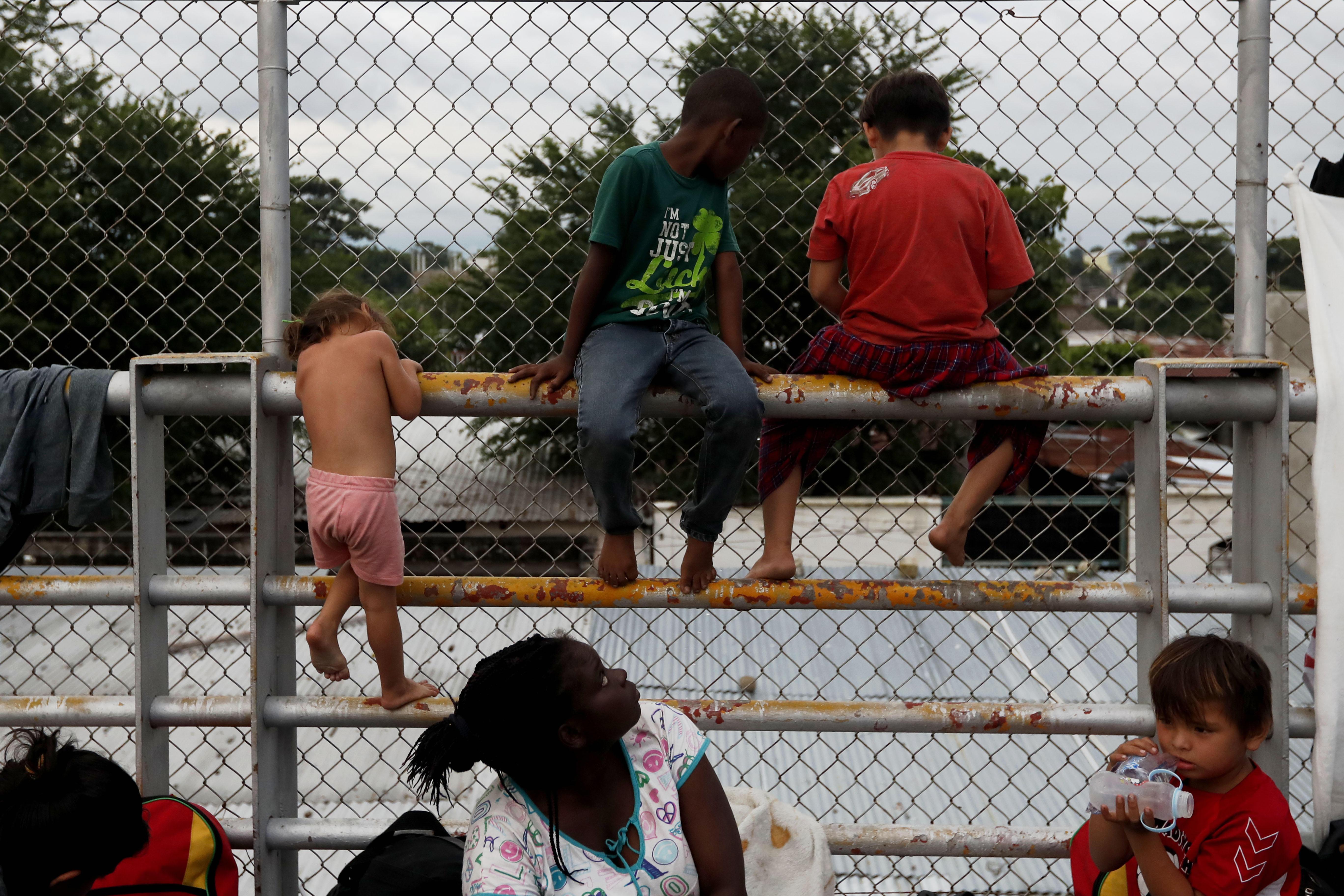 Grupos de migrantes hondureños esperan a poder entrar en México, en el puente que separa los dos países. (EFE/Esteban Biba)