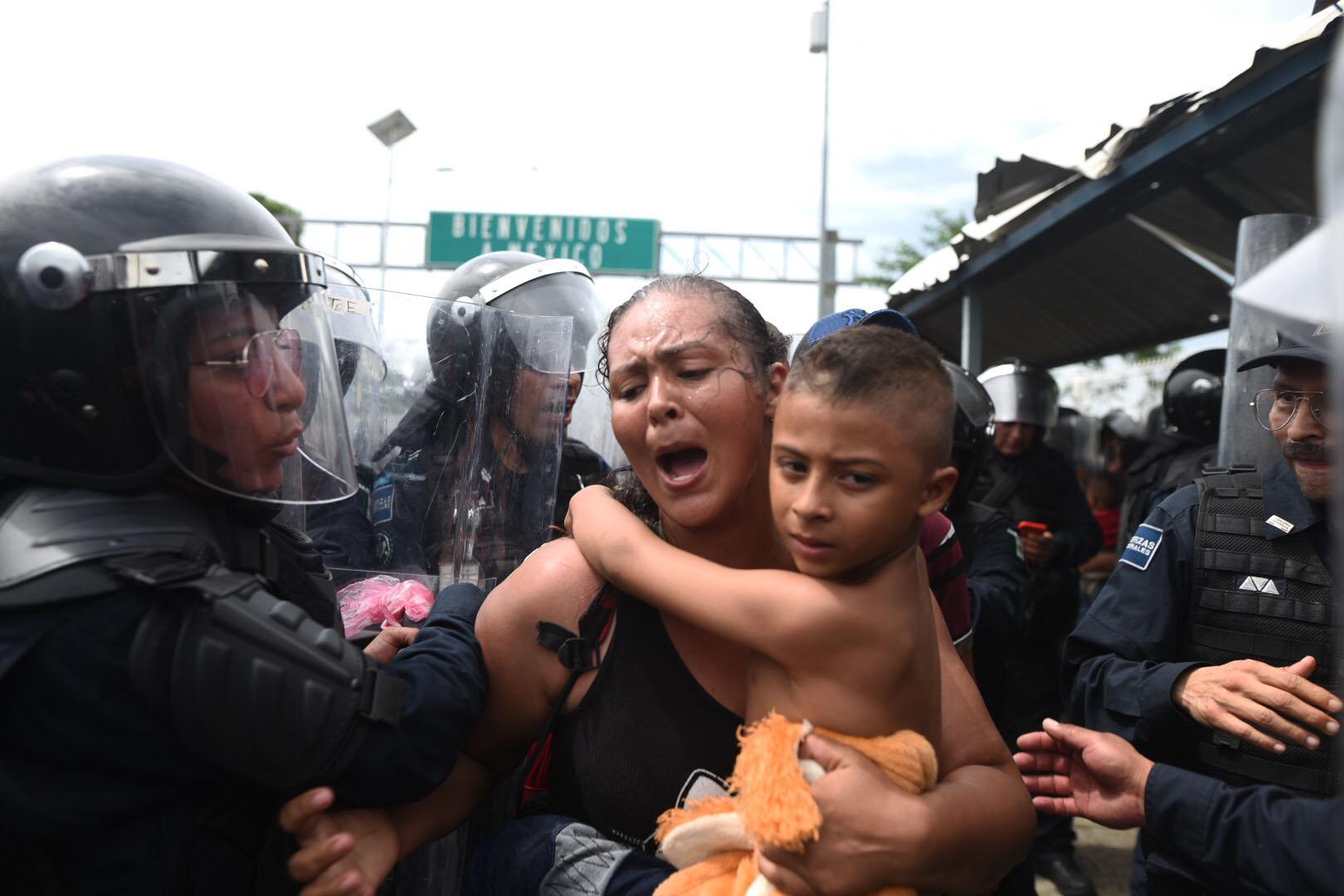 Miembros de la policía mexicana le impiden el pase a una migrante hondureña con su hijo en el paso fronterizo entre Guatemala y México. (EFE/Edwin Bercían)