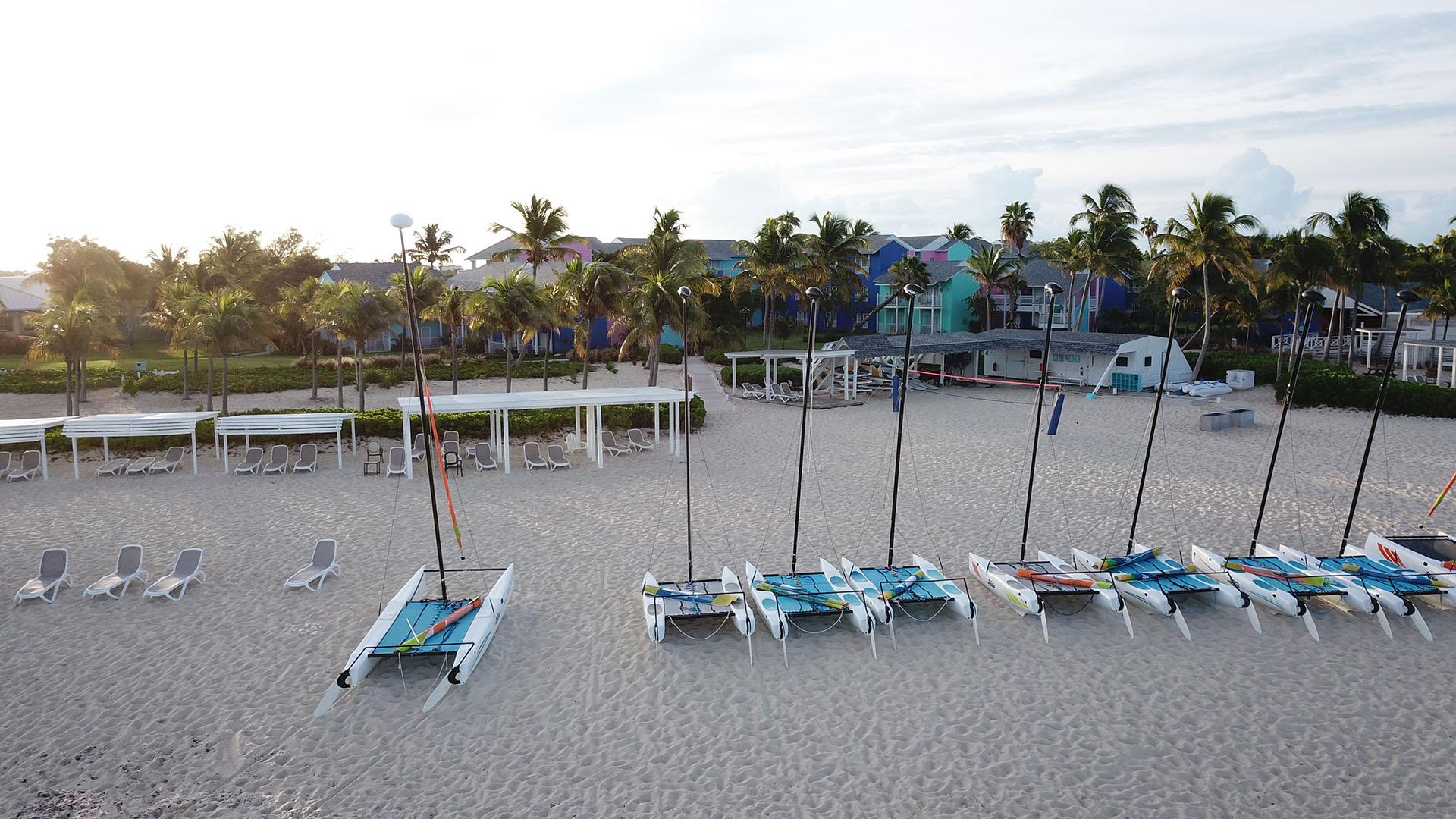 A lo largo de una playa de blanca arena que se extiende hasta el horizonte, los bungalows de colores se mezclan con los hibiscos