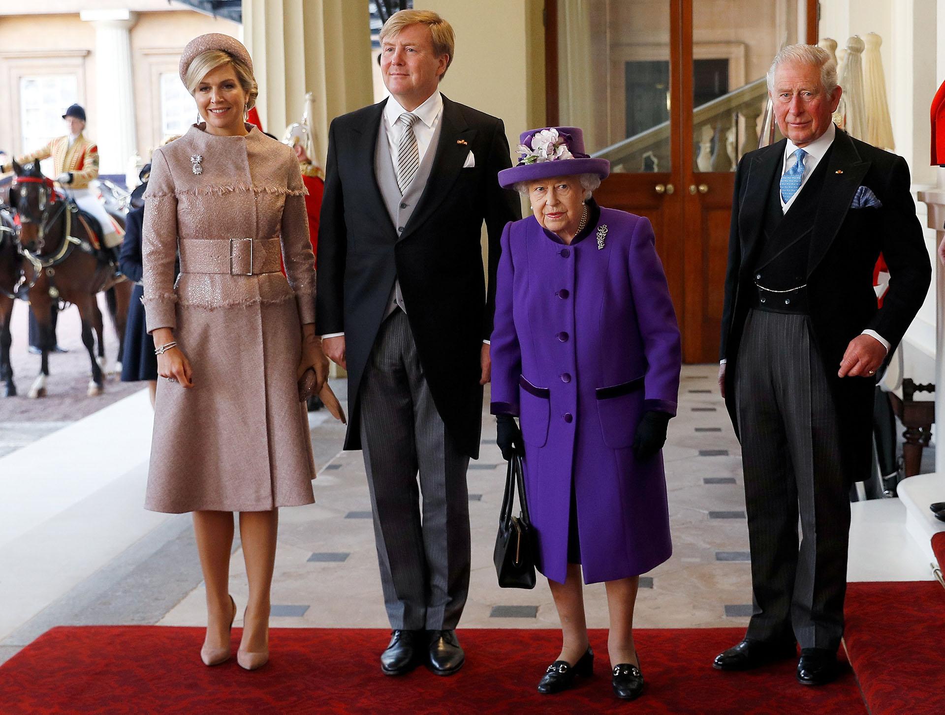 Los reyes en su primer encuentro con Isabel II, quien iba con un abrigo morado, acompañada de su hijo, el príncipe Carlos