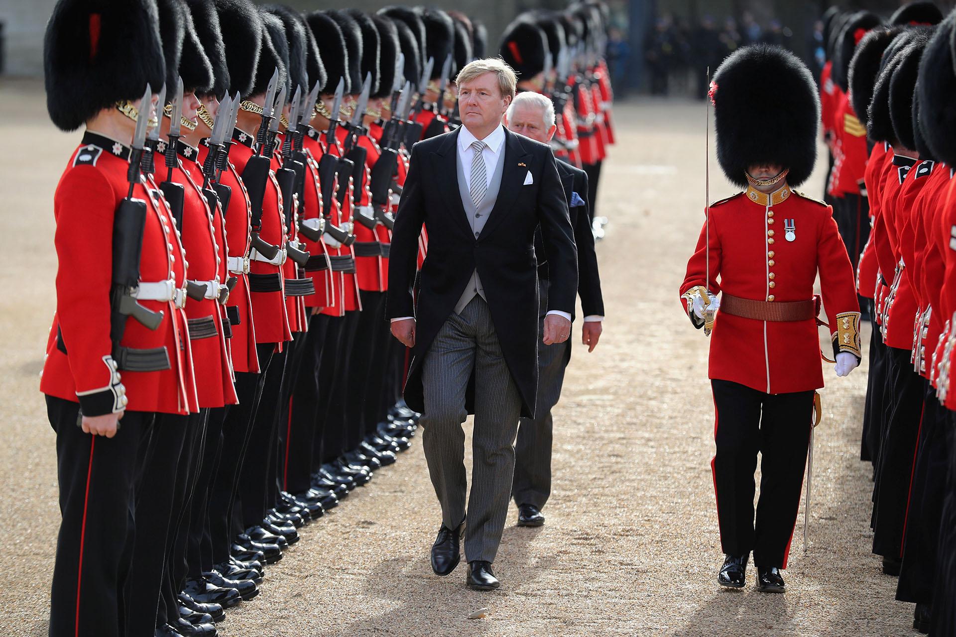 El rey de los Países Bajos y el príncipe Carlos caminan custodiados por la Guardia de Honor durante la bienvenida ceremonial al comienzo de una visita de Estado de dos días