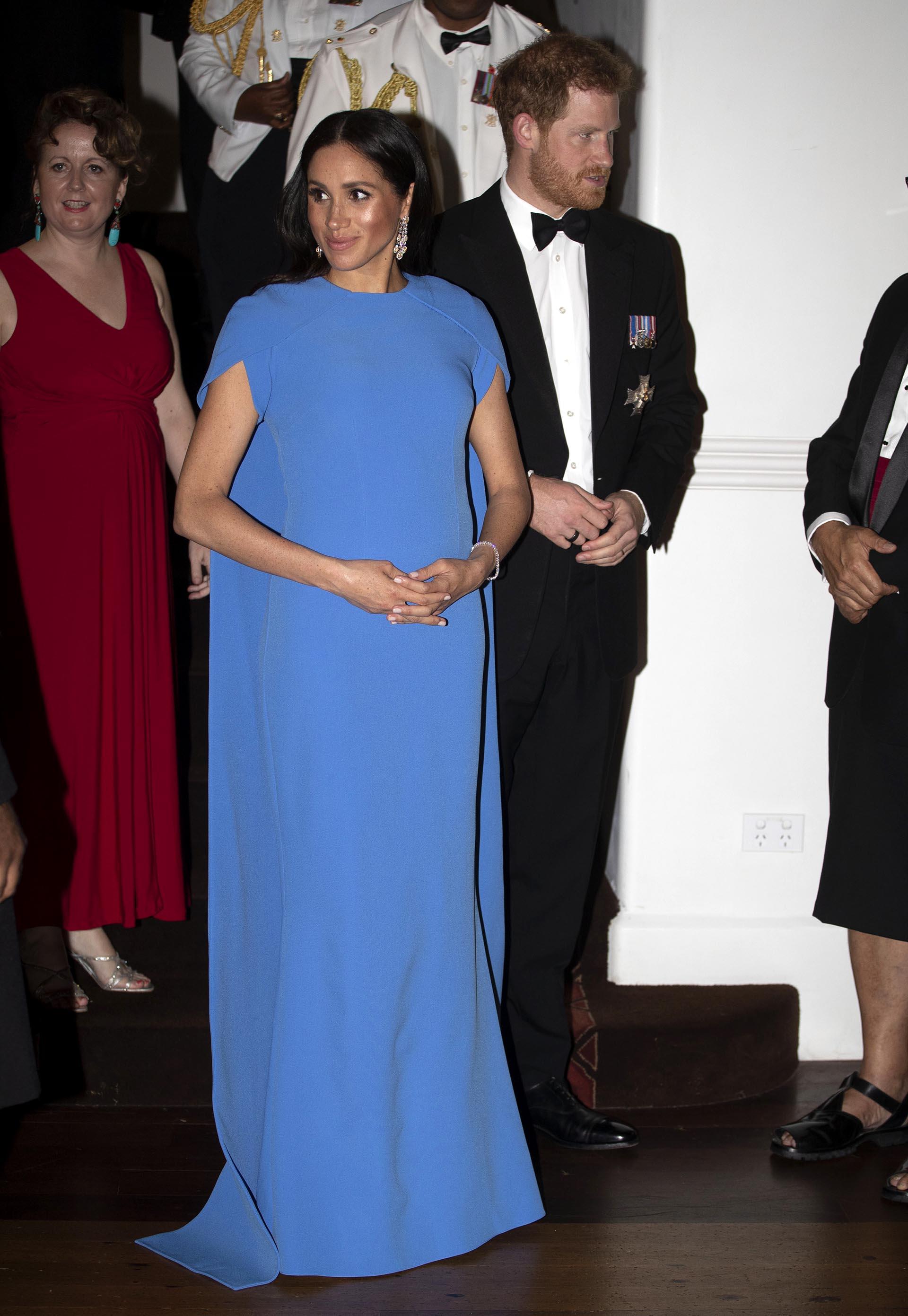 La duquesa de Sussex rindió homenaje a su país anfitrión cuando usó el vestido de ginkgo de Safiyaa en una cena de estado. El azul vibrante coincide con el tono que aparece en la bandera nacional de Fiji (AP Images)