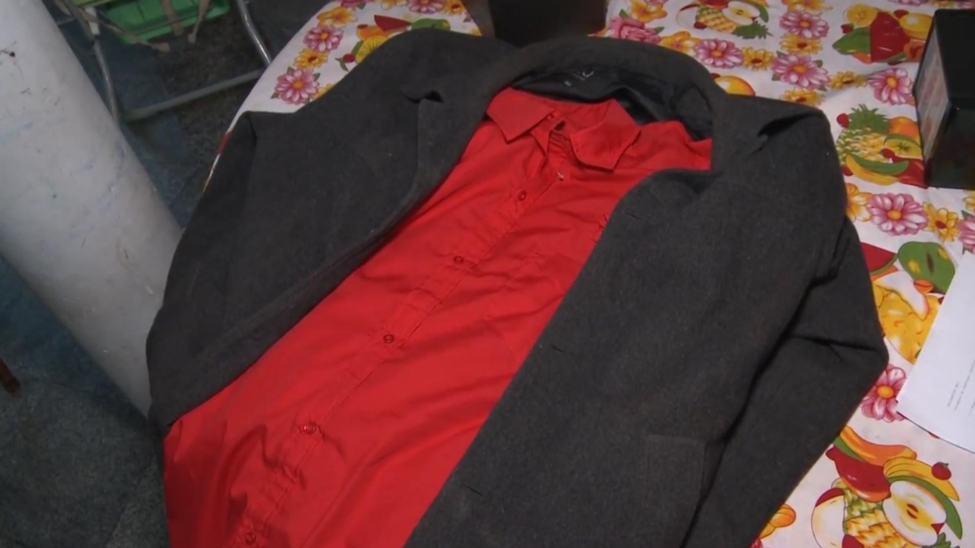 """El saco negro largo y la camisa roja que solía vestir el manosanta durante los ritos de """"limpieza""""."""