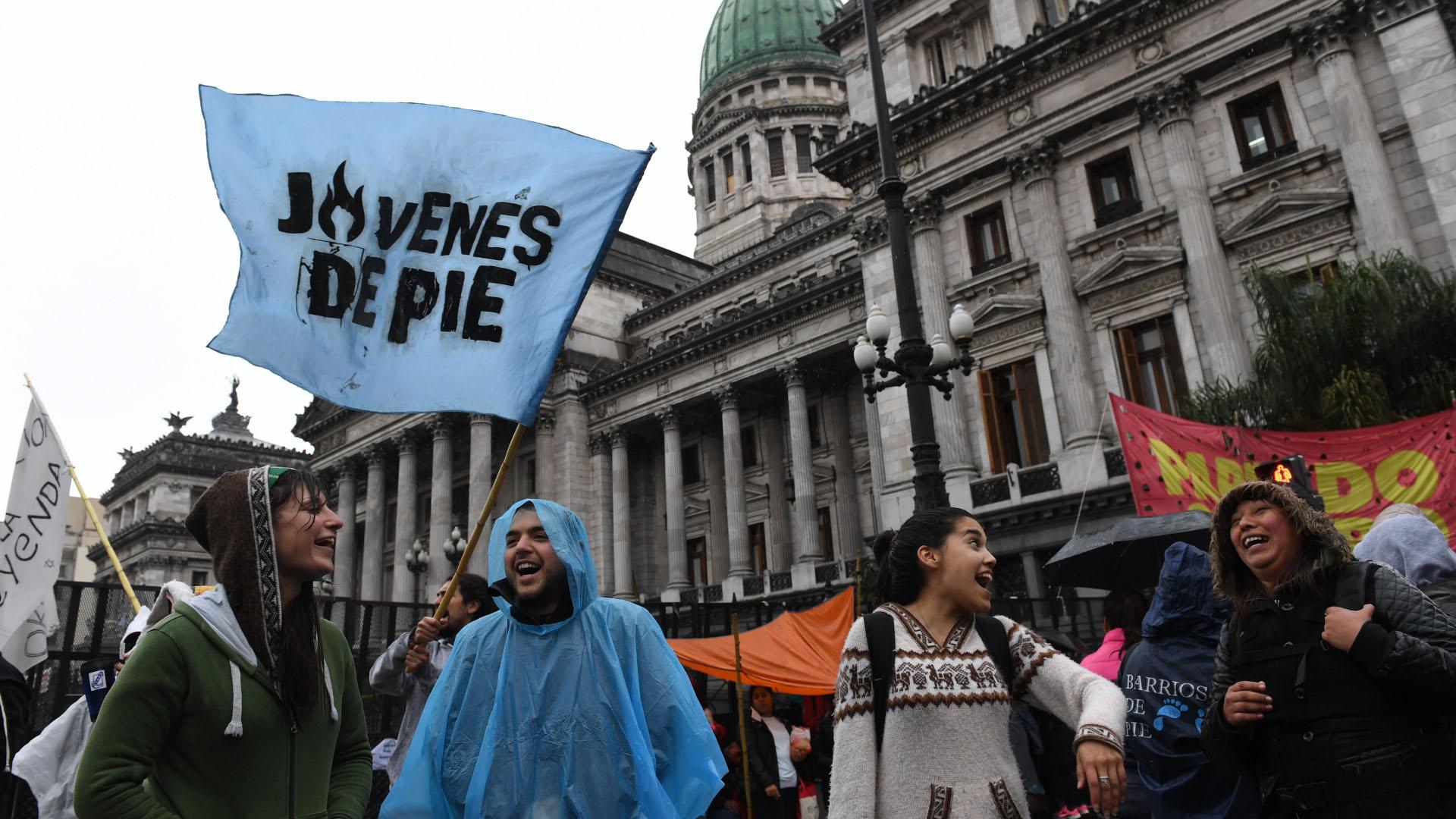 Bajo la lluvia: los manifestantes siguen el debate frente al Congreso (foto: Maximiliano Luna)