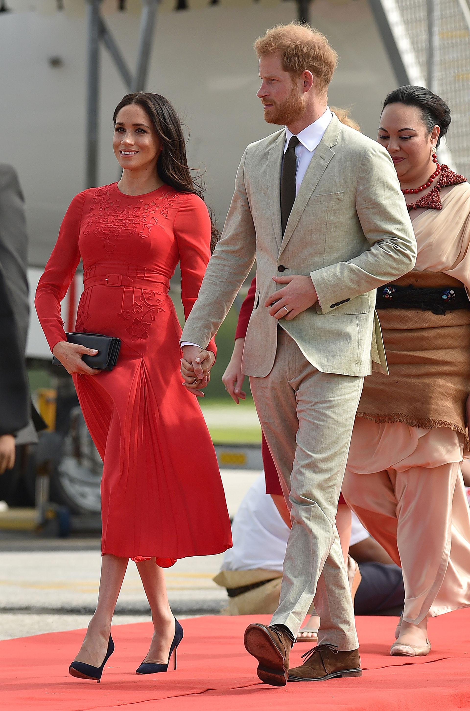El príncipe Harry y la duquesa de Sussex llegaron al aeropuerto de Fua'amotu en Tonga el 25 de octubre de 2018.En esta ocasiónoptó por un deslumbrante vestido rojo fuegode Self Portrait (AFP)