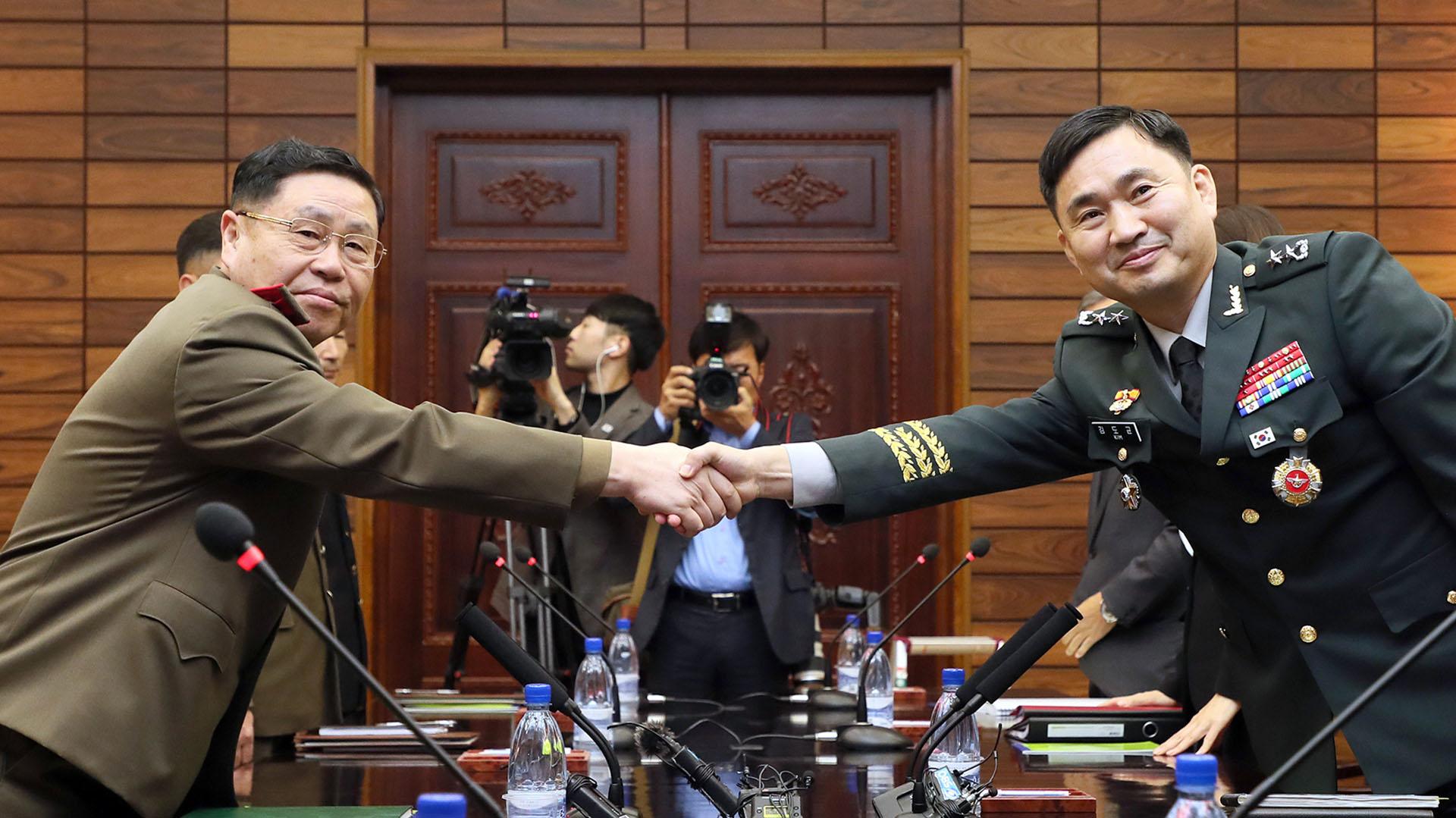 El general Kim do-Gyun (Corea del Sur) estrechando la mano con su homólogo norcoreano Un San durante sus conversaciones militares de nivel general en el lado del norte de la aldea de la tregua de Panmunjom en la zona desmilitarizada (AFP PHOTO / South Korean Defence Ministry)