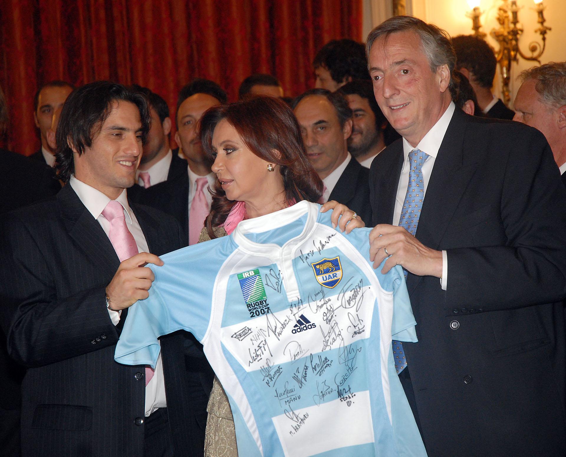 El presidente Néstor Kirchner, la senadora Cristina Fernández de Kirchner y el medio scrum Agustín Pichot con una camiseta autografiada de los Pumas durante la visita del seleccionado argentino de rugby a la Casa de Gobierno.