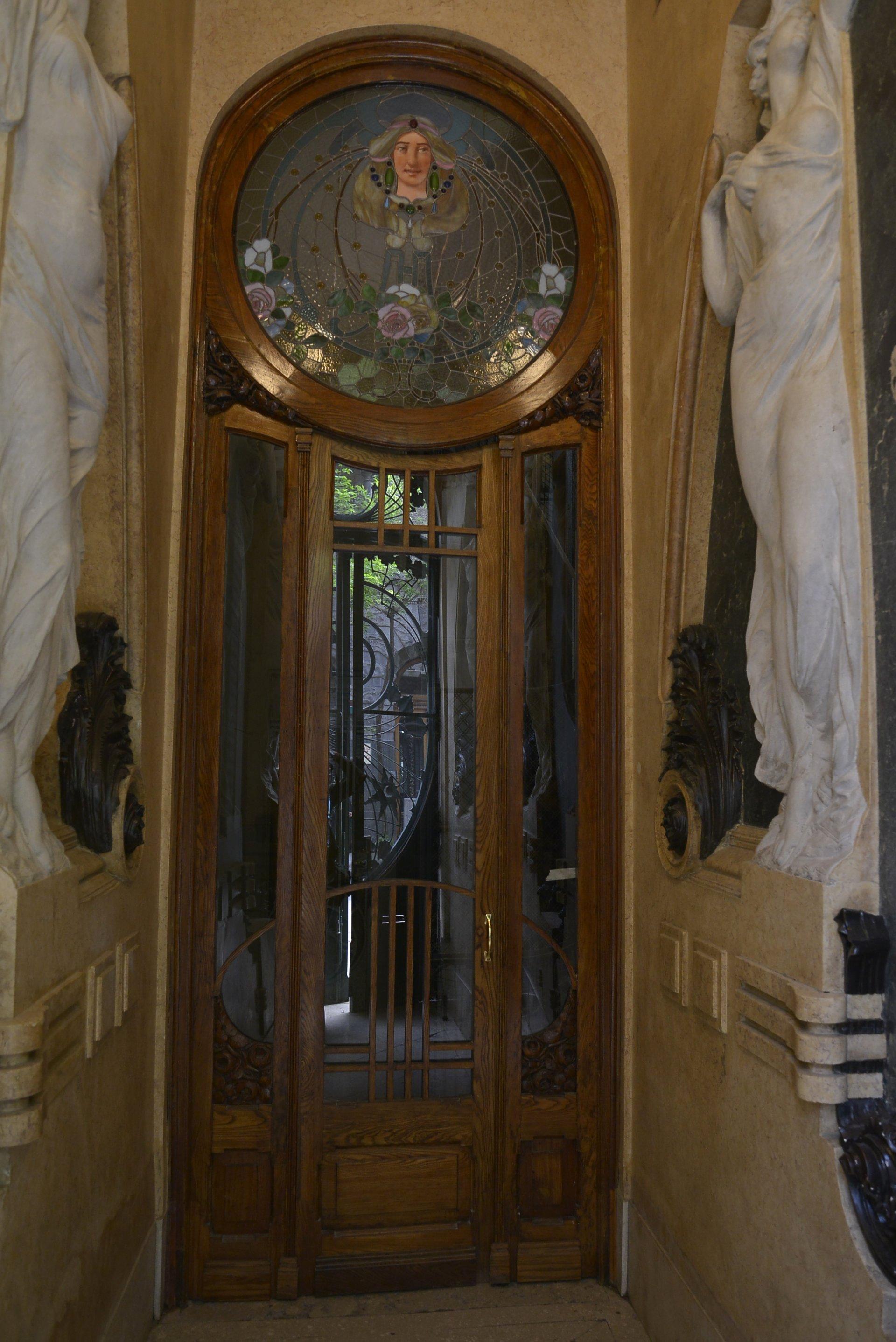En las puertas de maderas antiguas hay decoraciones de vitreaux de figuras femeninas y flores