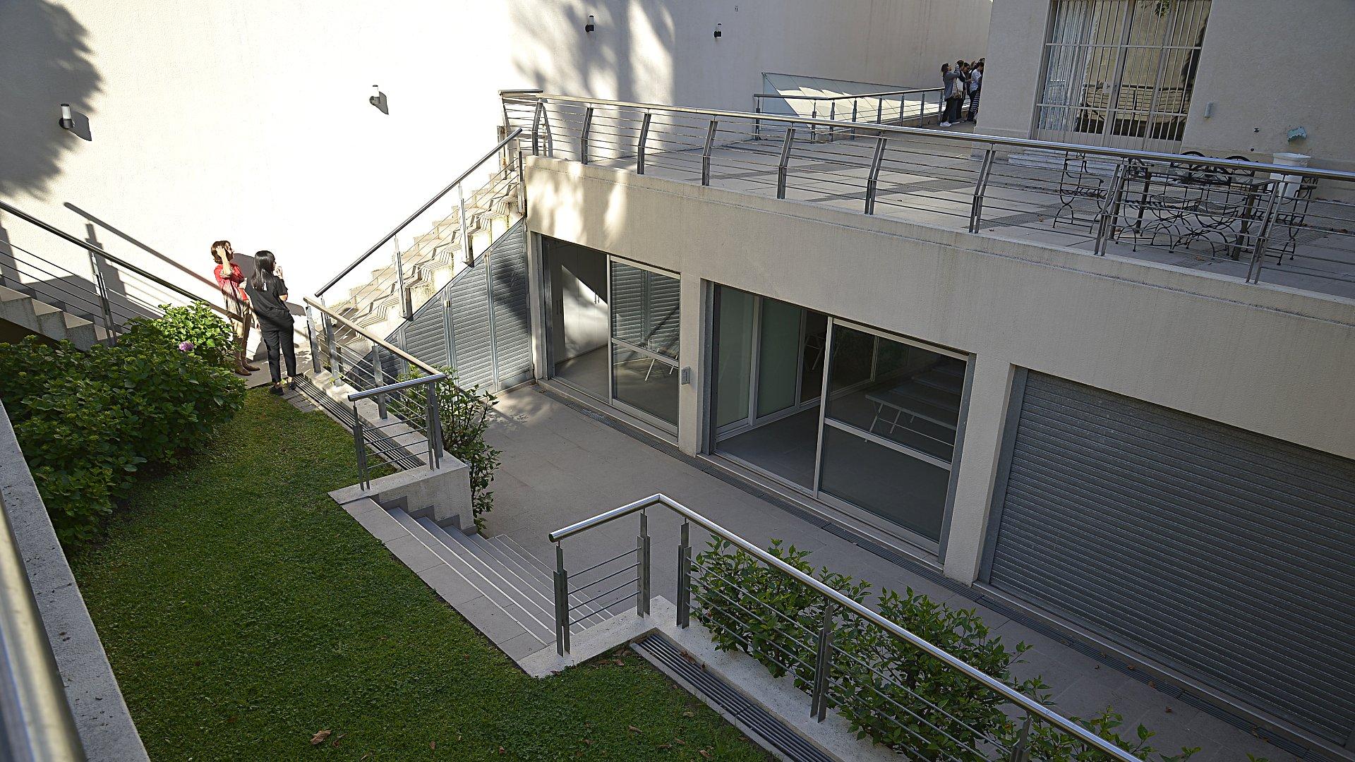 El jardín del interior de la casa. Escaleras y ventanales de vidrio. Una fachada interna moderna