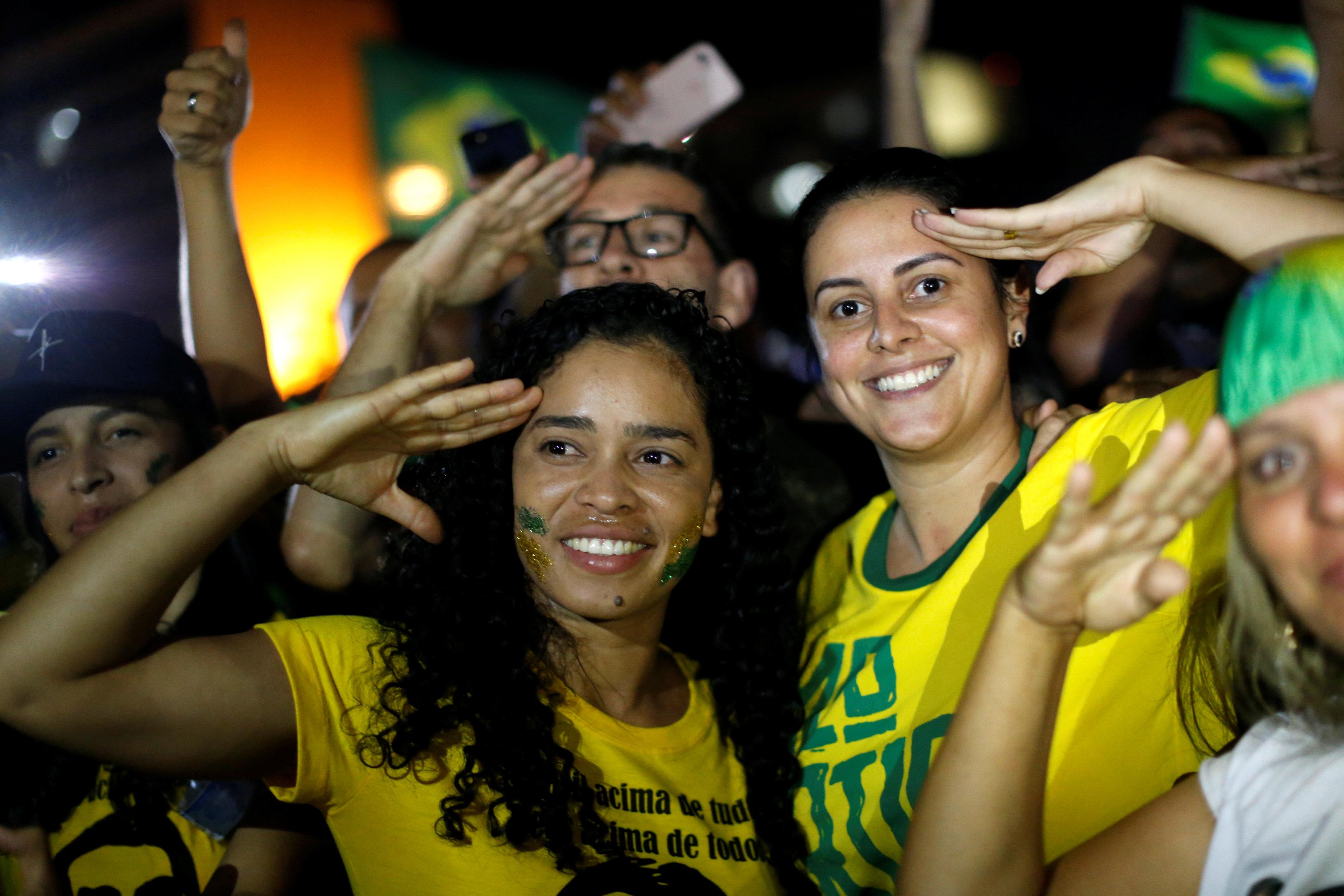 Simpatizantes de Bolsonaro celebran en Brasilia el resultado de la elección con el típico gesto del candidato derechista(REUTERS/Adriano Machado)