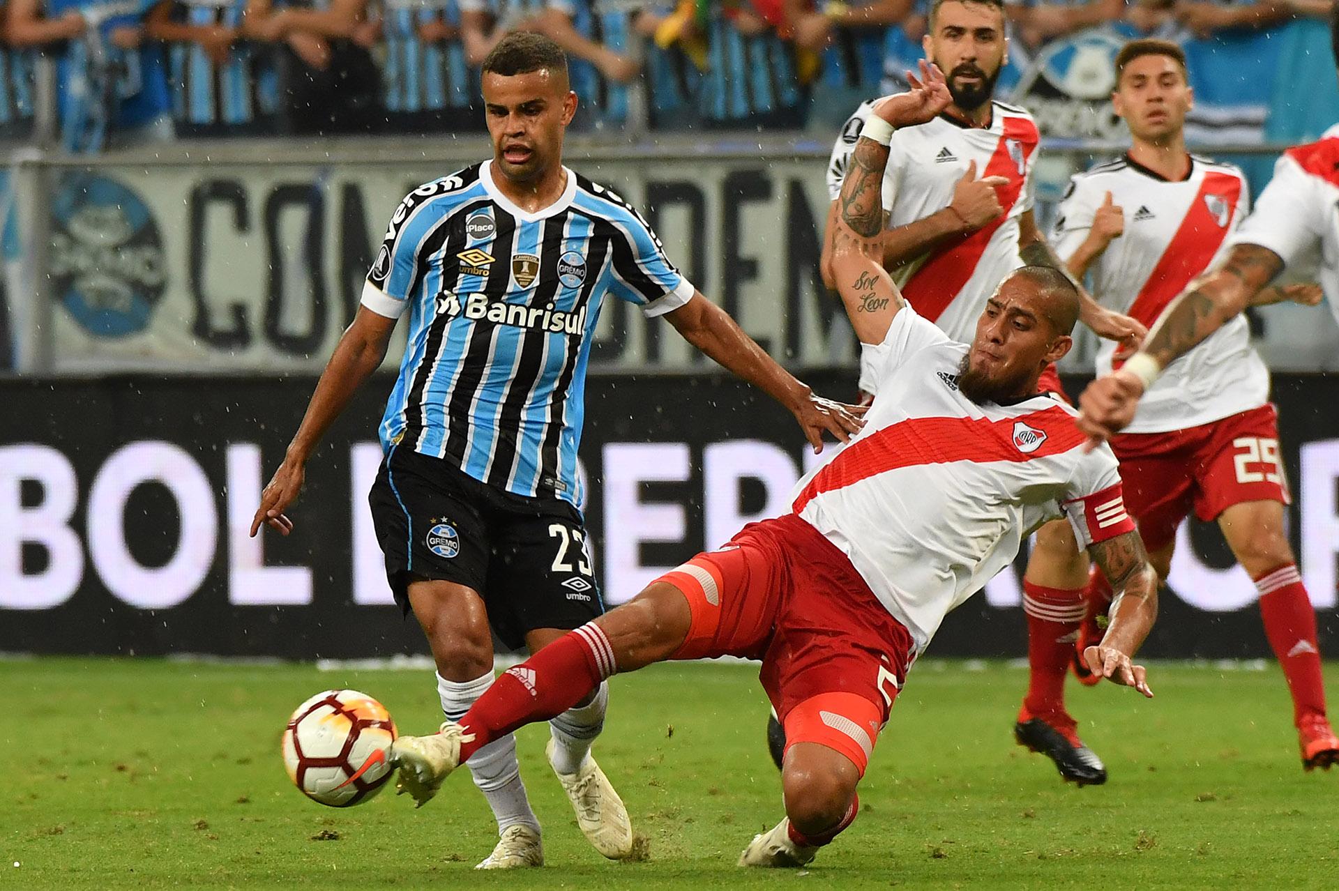 Alisson, de Gremio de Porto Alegre, mira la pelota que le quita Jonatan Maidana (AFP)