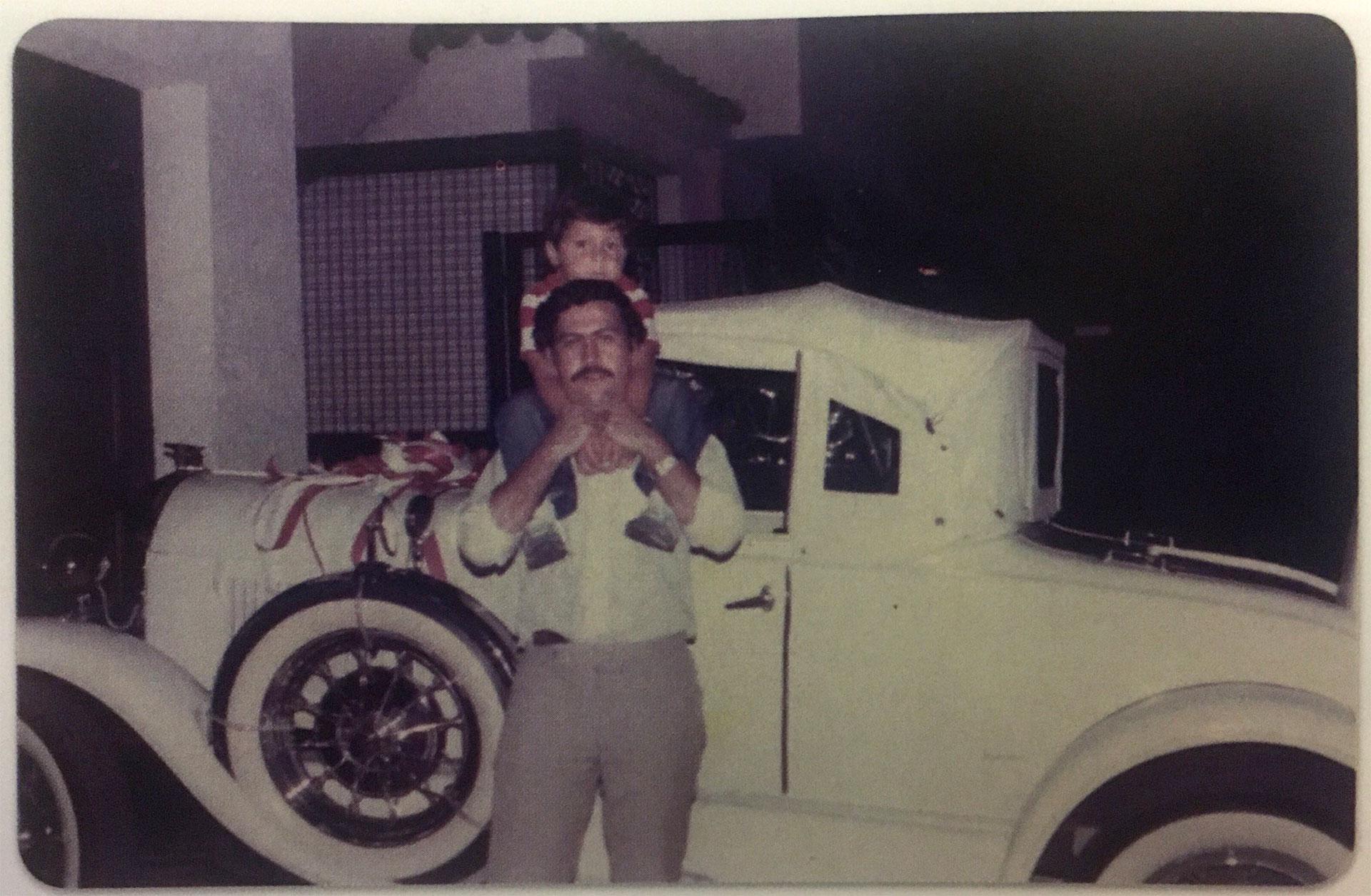 1979. Pablo Escobar sosteniendo por los hombros a su hijo Juan Pablo. Era el cumpleaños número 30 del capo narco y Victoria Henao había decidido regalarle el automóvil antiguo que está detrás suyo (Victoria Eugenia Henao / Editorial Planeta)