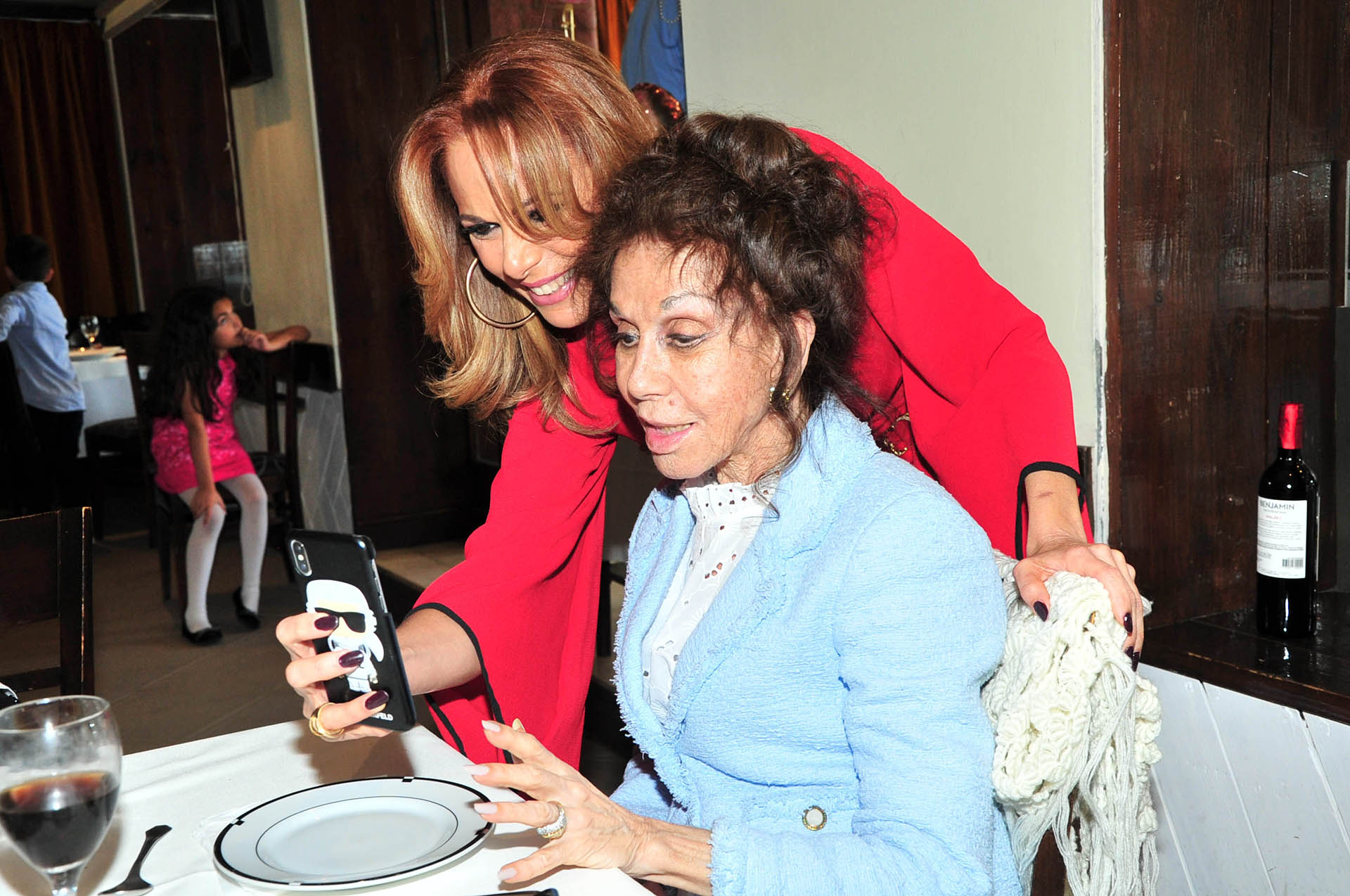 Iliana Calabróríe mientras le muestra algo en el celular a su madre, Coca