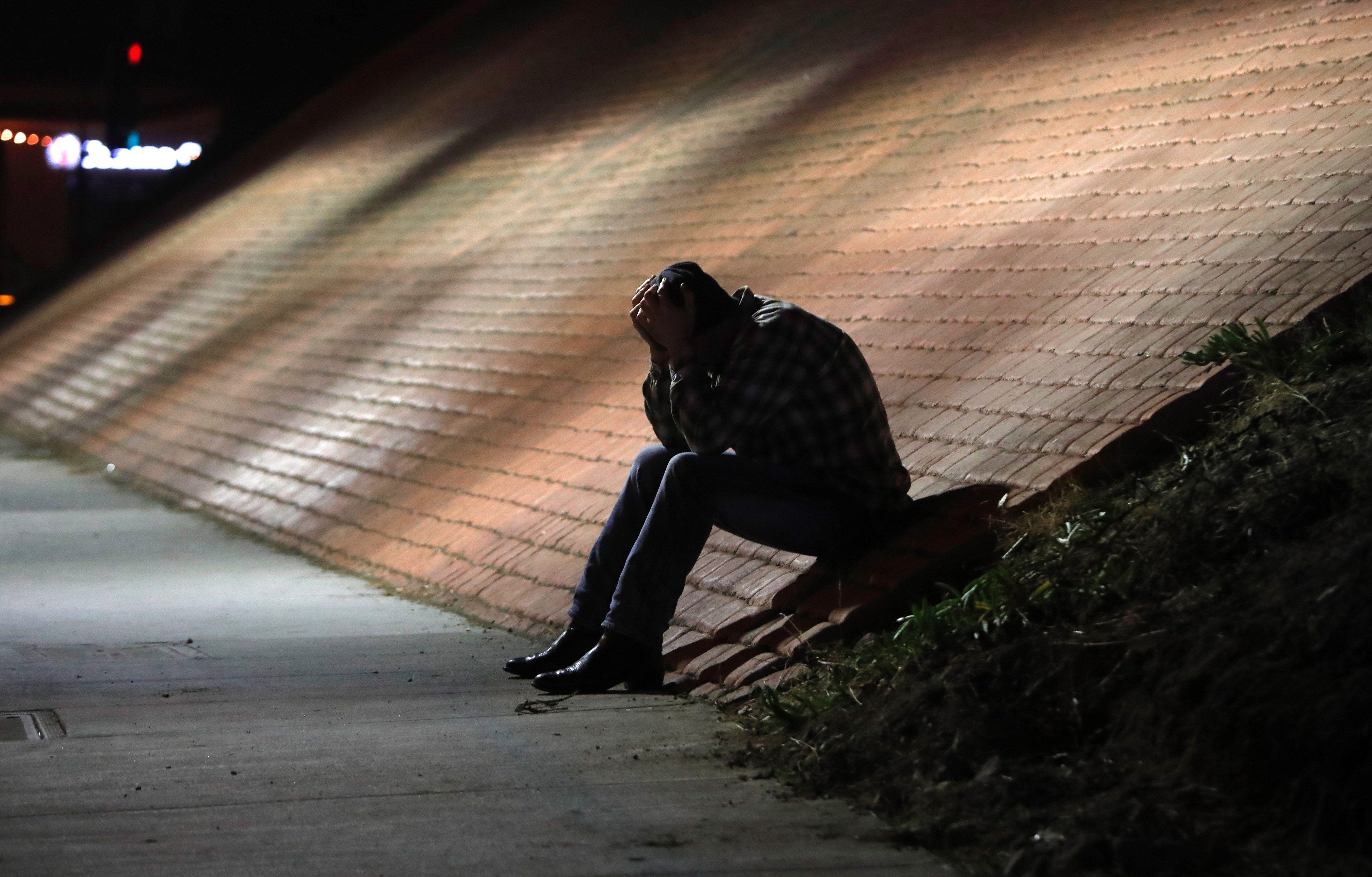 Un hombre se muestra afligido cerca del lugar del tiroteo en el bar Borderline