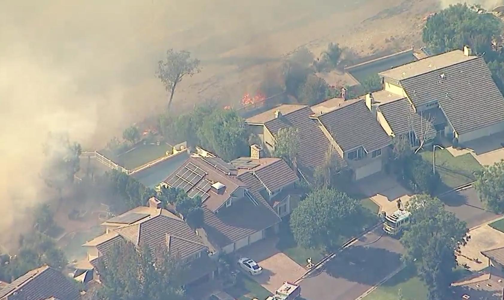 En esta imagen tomada al mediodía del viernes, las llamas alcanzan el fondo de uno de los vecindario bajo orden de evacuación obligatoria