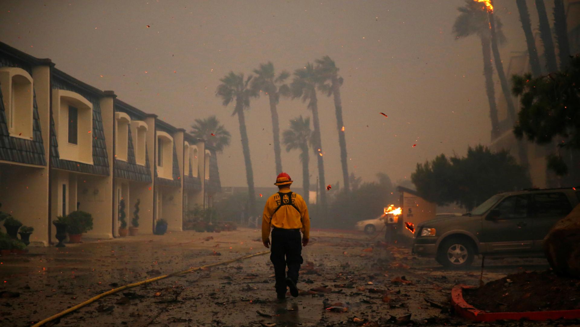 Un bombero camina por zona aledaña que aún no ha sido devastada por el incendio. (Reuters)